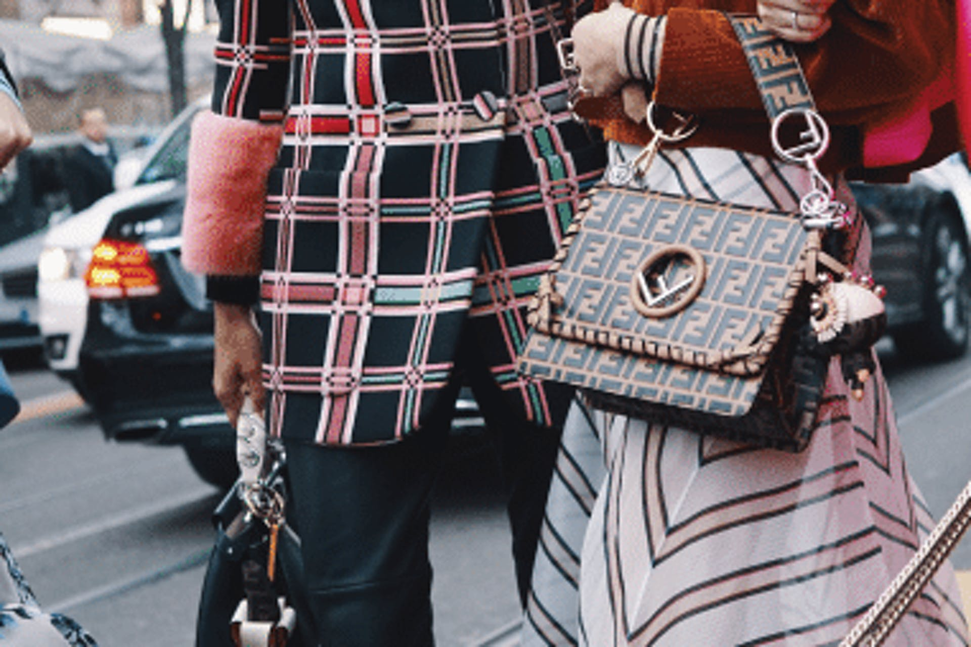 Two women, one with a handbag both wearing patterned clothing.