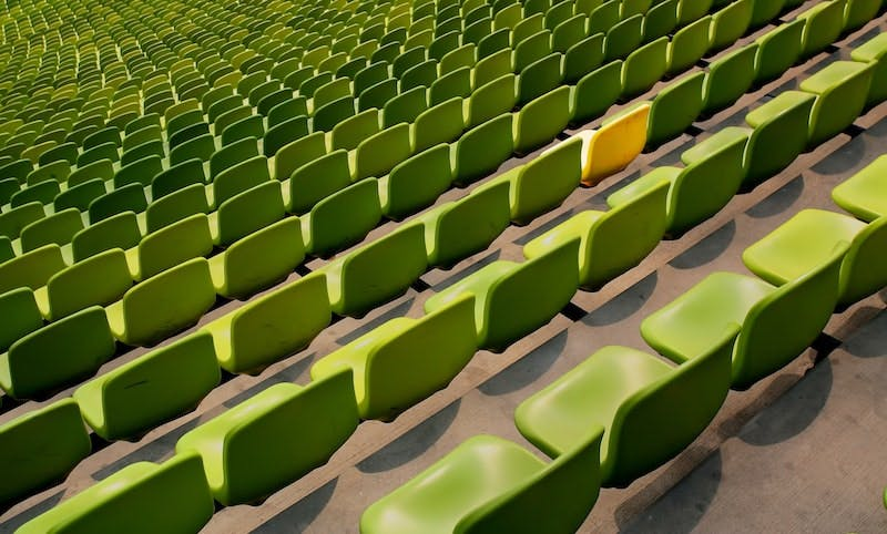 Green stadium seats, among them is a yellow one