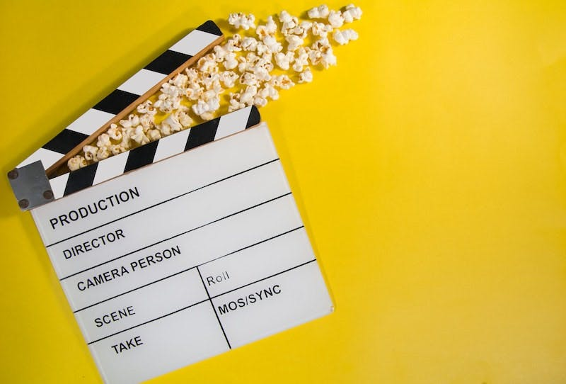 A clapperboard on a yellow background, popcorn is coming out of it