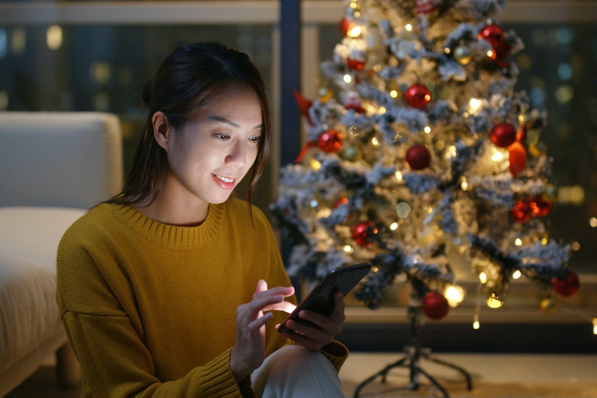 Junge asiatische Frau sitzt mit ihrem Smarthphone vor einem Weihnachtsbaum