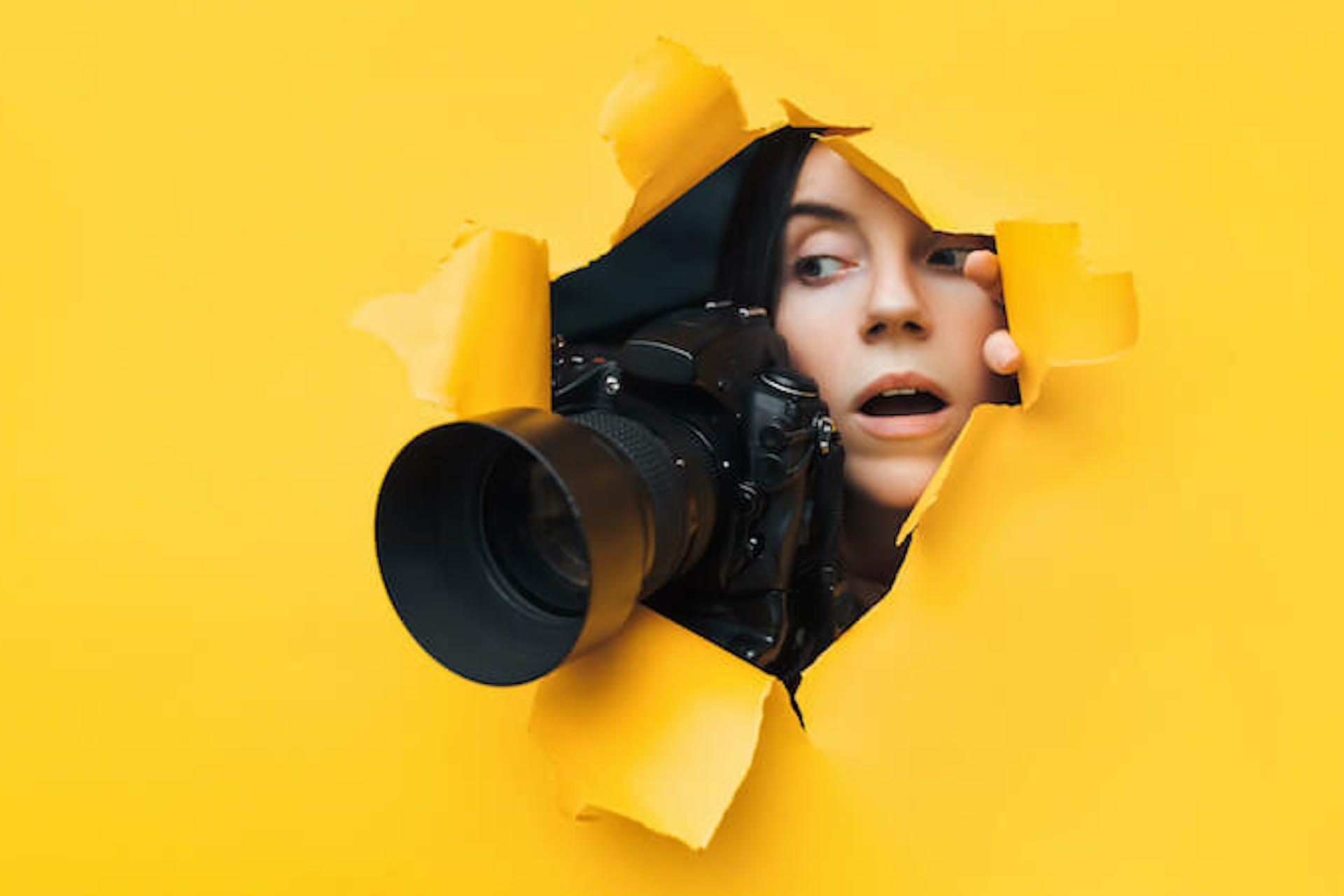 Man sieht eine junge Frau mit einer Kamera mit einem großen Objektiv durch eine gelbe Pappwand luken. Das Bild ist Header für unseren Beitrag zu elektronischen Pressespiegeln.