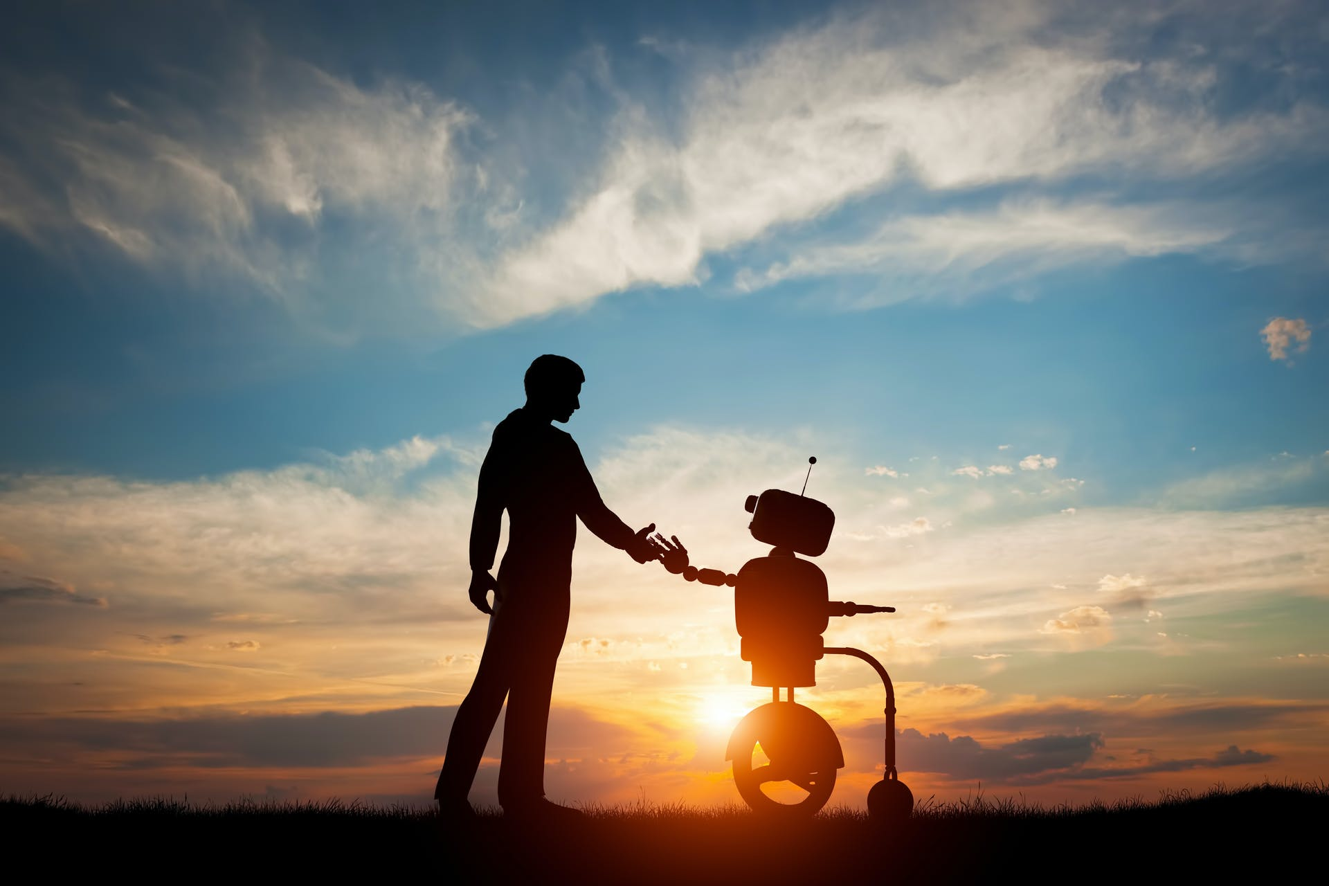 A man holding a robot's hand whilst standing in front of a sunset.