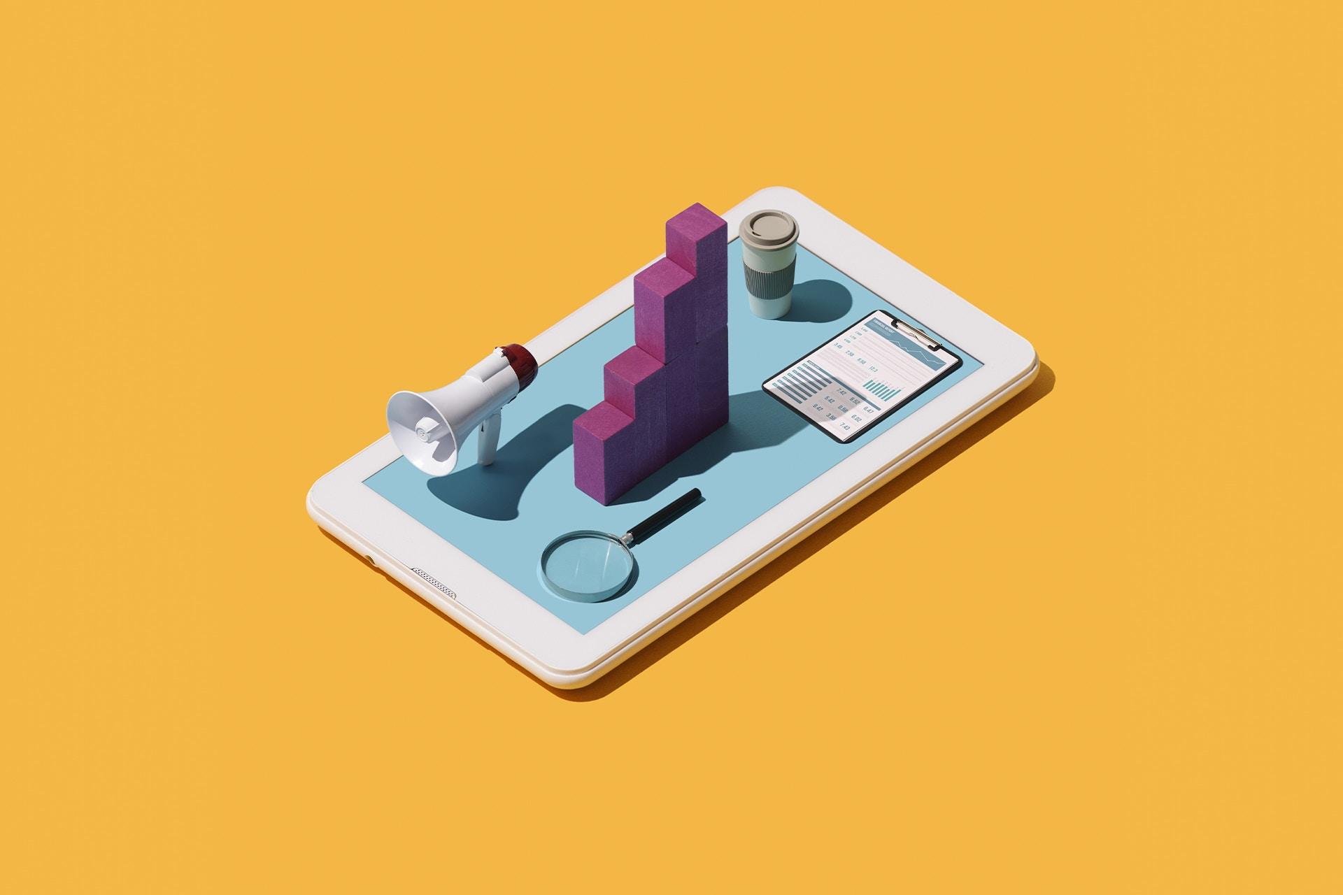 Un fond jaune uni avec une tablette au centre. La tablette était recouverte de divers objets, tels qu'un mégaphone, une loupe, un presse-papiers et un grand graphique à barres. Les objets pourraient tous être utilisés par les spécialistes du marketing analysant le Big Data pour mettre en place une campagne marketing basée sur les données.