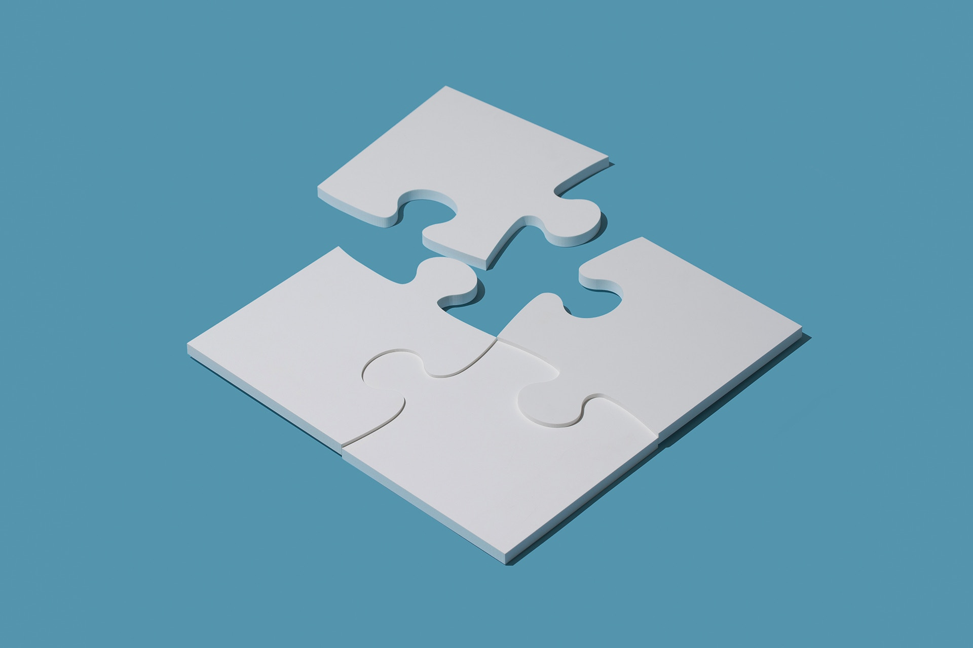 A 4-piece puzzle in the shape of a square with one corner not yet connected on a blue background. This image is being used a thumbnail for a blog onmarketing segementation