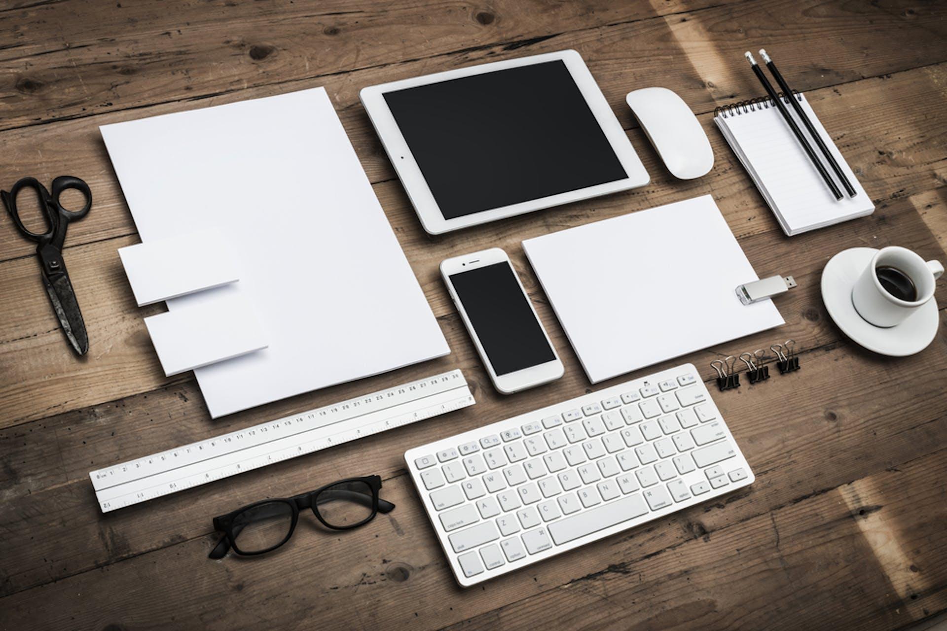 Man sieht ein Foto eines Holztisches mit ungebrandeten, weißen Utensilien darauf. Das Foto ist das Titelbild unseres Beitrags zur Erstellung einer Corporate Identity.