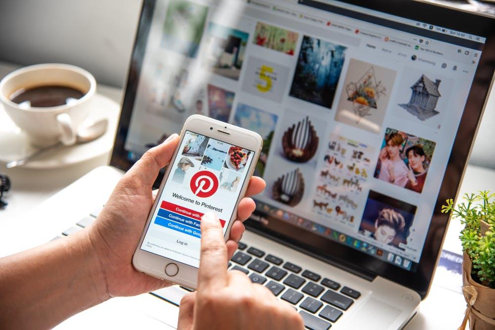 Mit Kaffe vor Laptop und Smartphone mit Pinterest