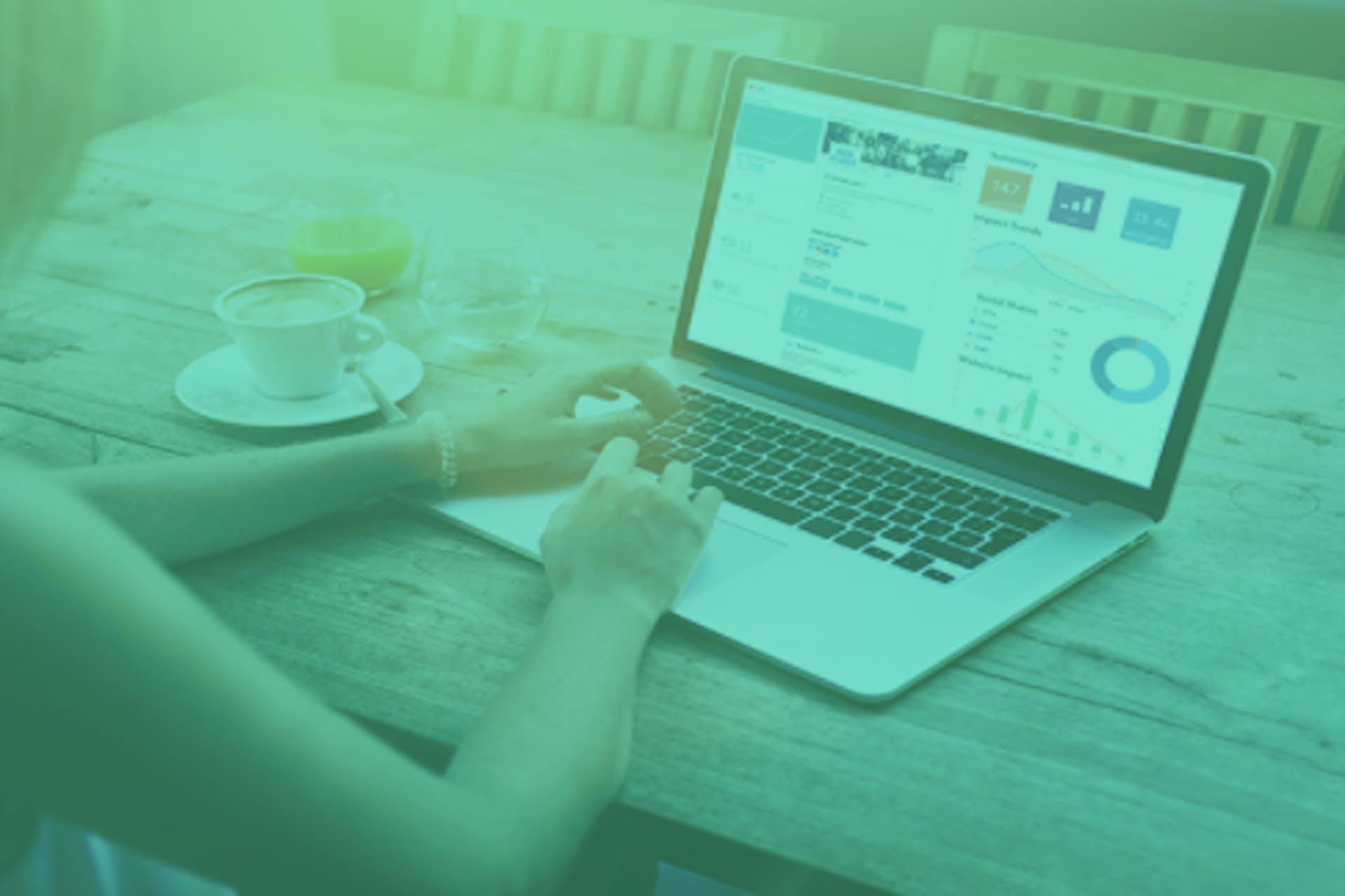 Foto von Frau, die an ihrem Laptop arbeitet mit einem offenen Dashboard an Daten
