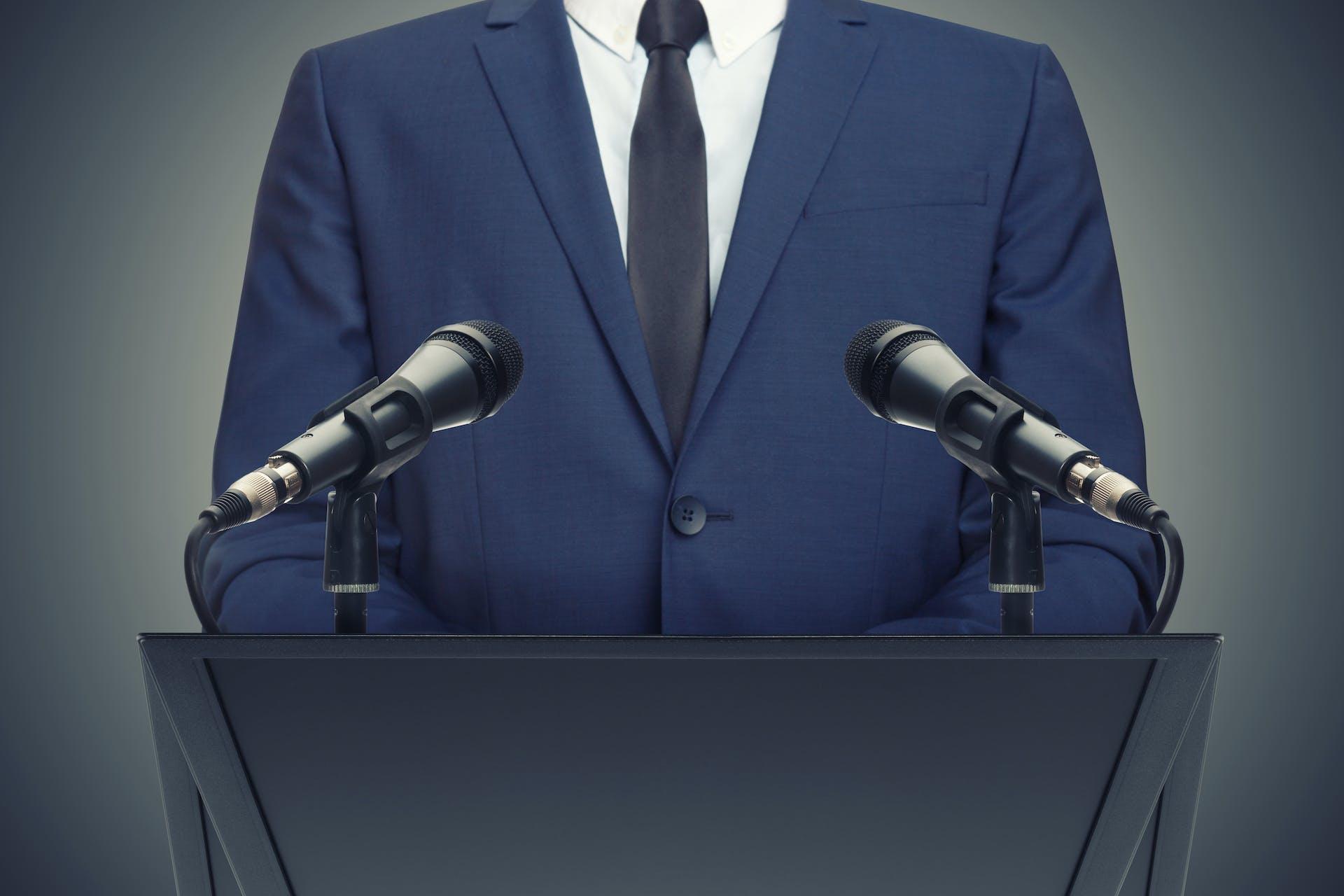 Man sieht ein Bild von einem Mann im Anzug vor einem Podium mit zwei Mikrofonen stehen. Dabei soll es sich um einen Politiker handeln. Dieses Bild ist das Titelbild unseres Beitrags zum Thema wie Social Media die Politik beeinflusst.