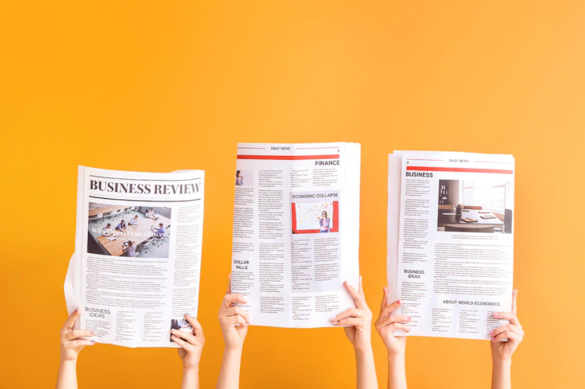 Sanomalehtiä piteleviä käsiä vierekkäin