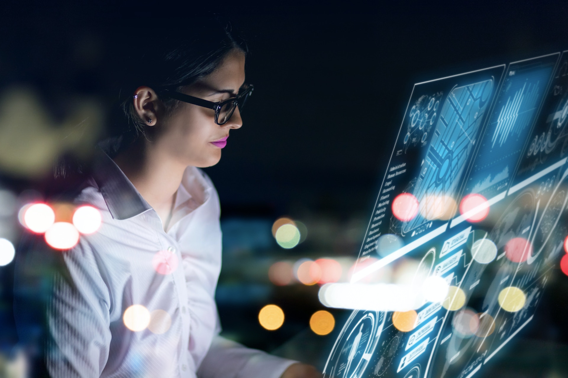 woman wearing glasses and working on a computer screen