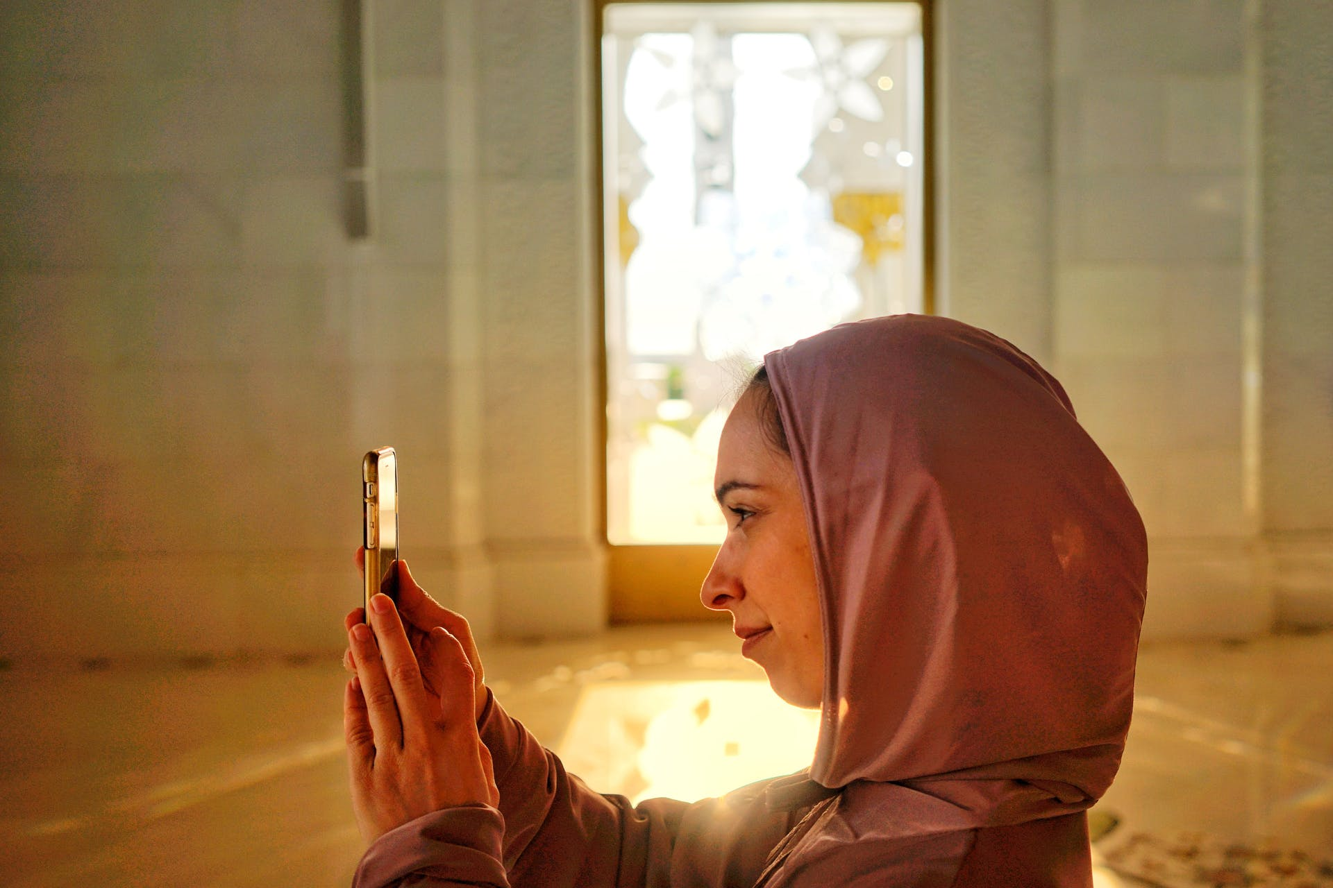 arabian woman holding her smartphone to take a photo