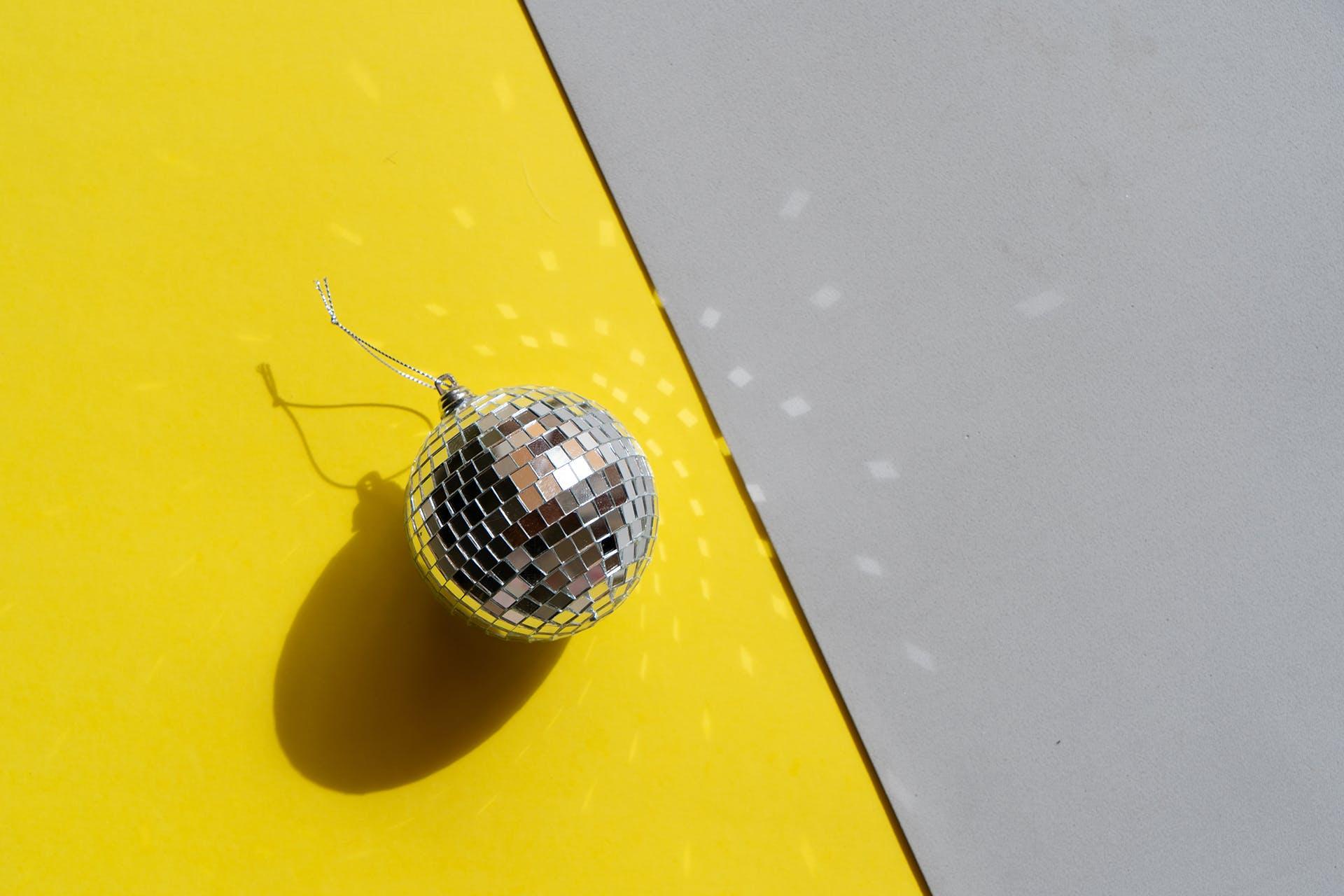 Mini disco ball on yellow and grey background