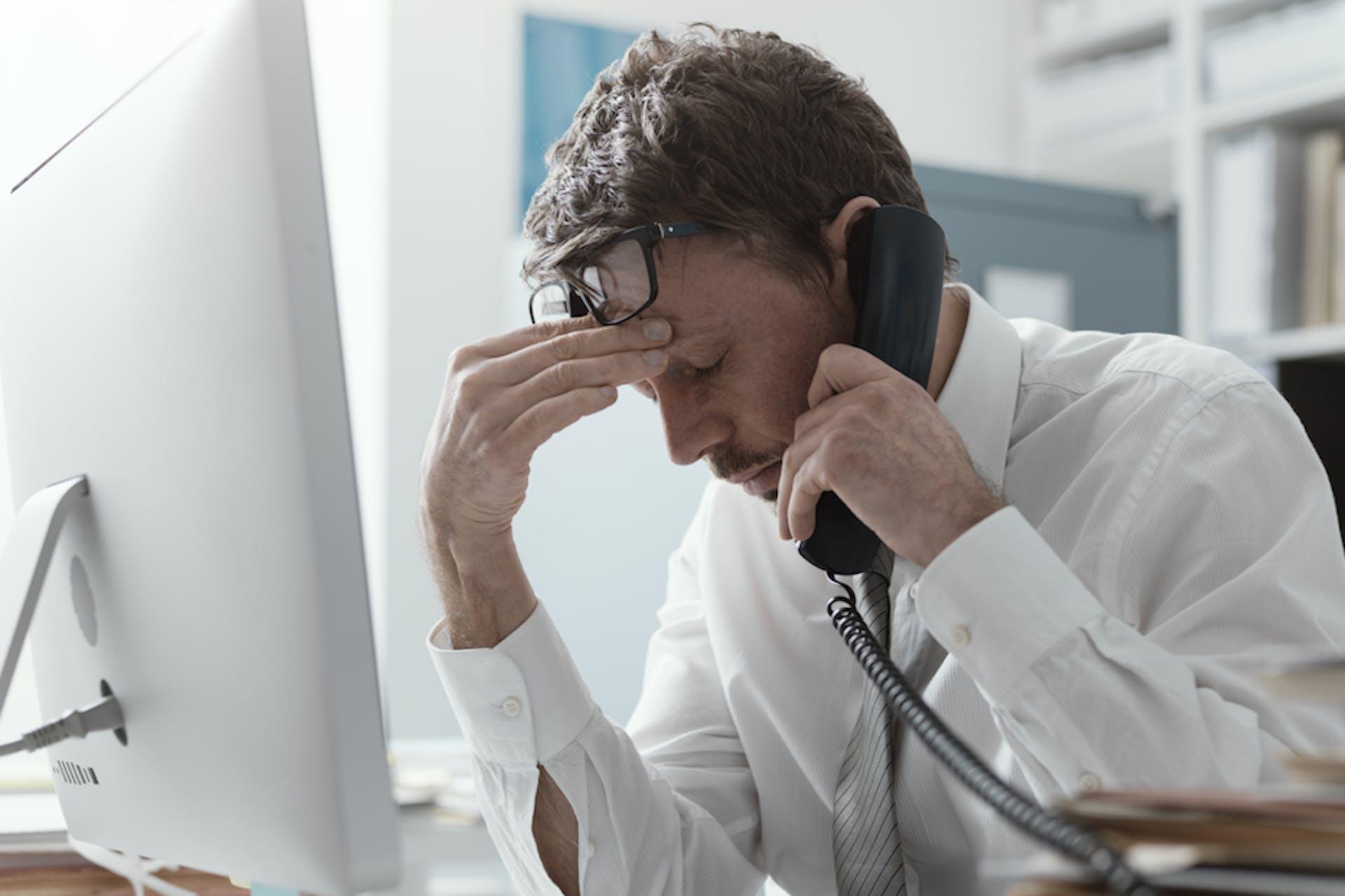 A man using a landline telephone at his work desk