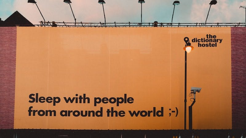 """A billboard promoting the Dictionary hostel, the phrase """"Sleep with people from around the world"""" is displayed"""