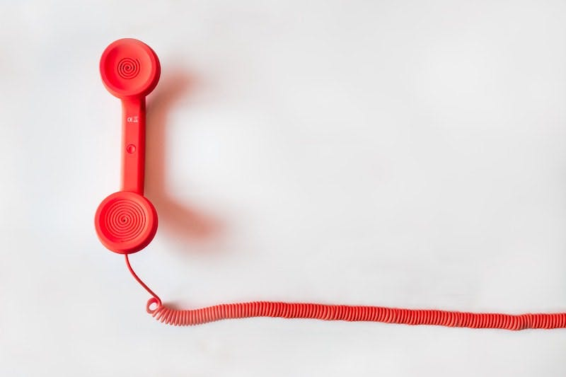 A red corded phone on a white background