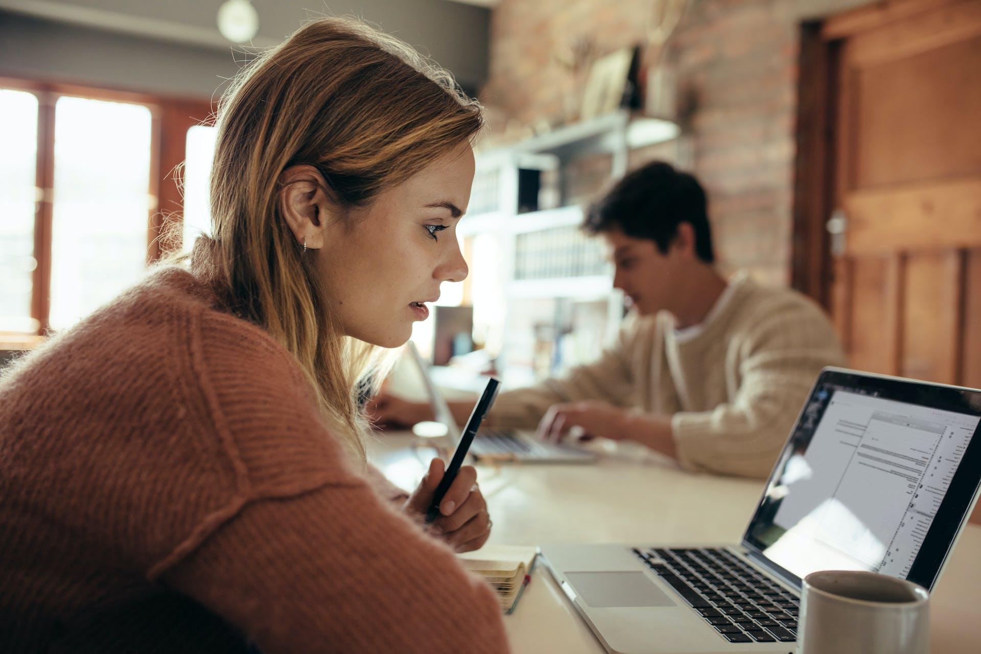 Junge Frau sitzt im Cafe und schaut auf ihren Laptop