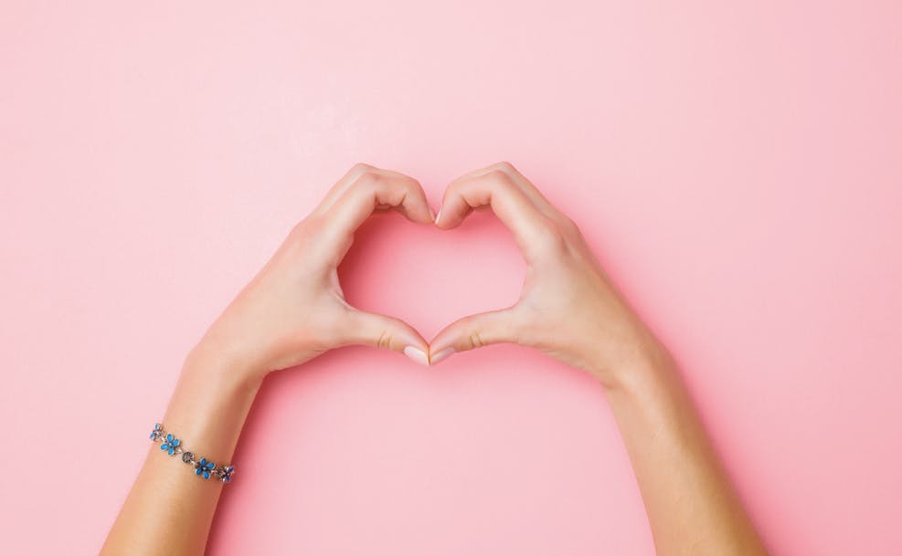 pink background with hands forming a heart