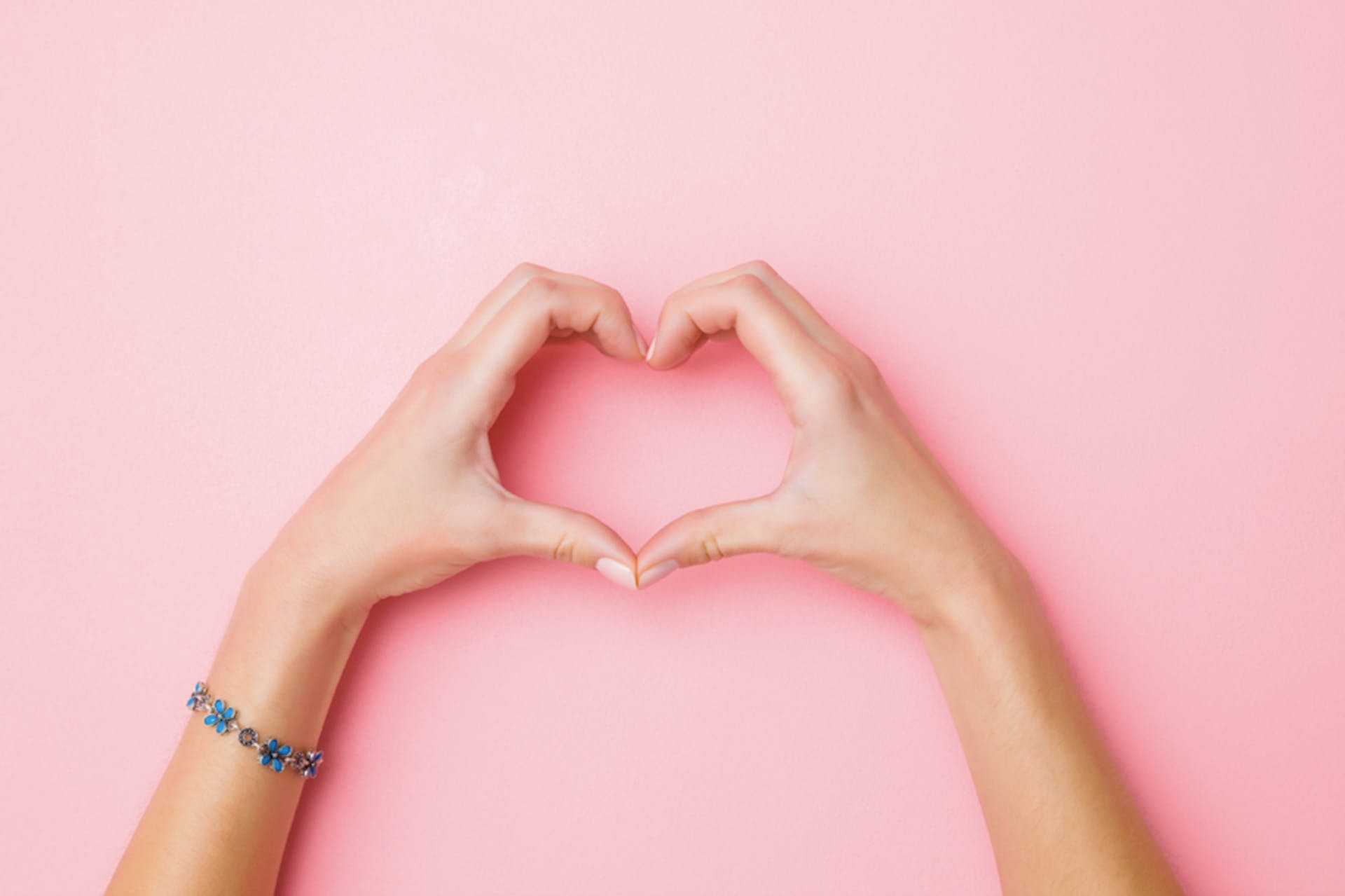 hand creating a heart shape against a pink background
