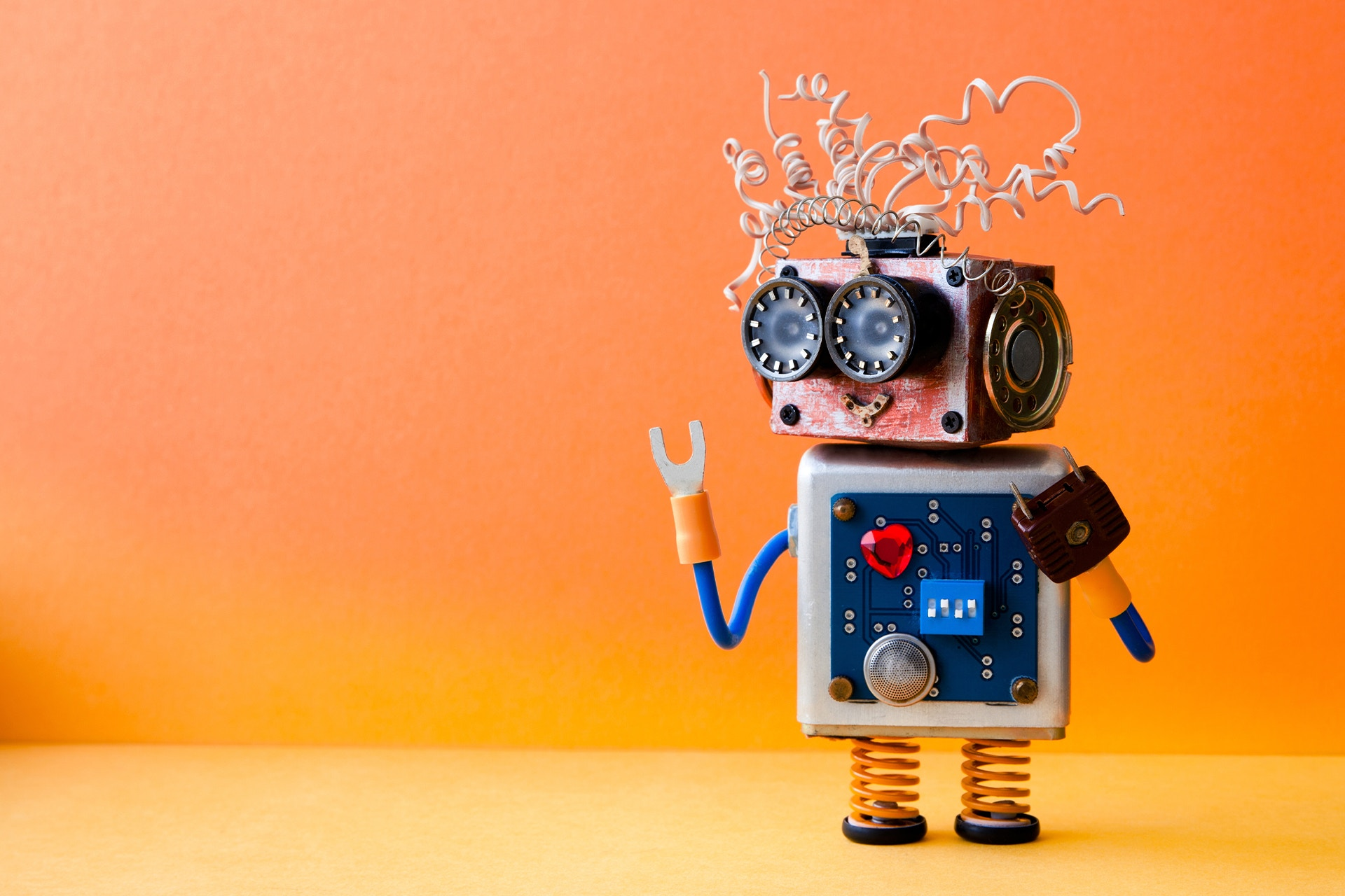 A toy robot that has been made using scraps of pieces from different machines or mechanical parts, like springs, electrical plugs, and wires. He could be social-savvy bot answering questions around how to build similar social media bots.