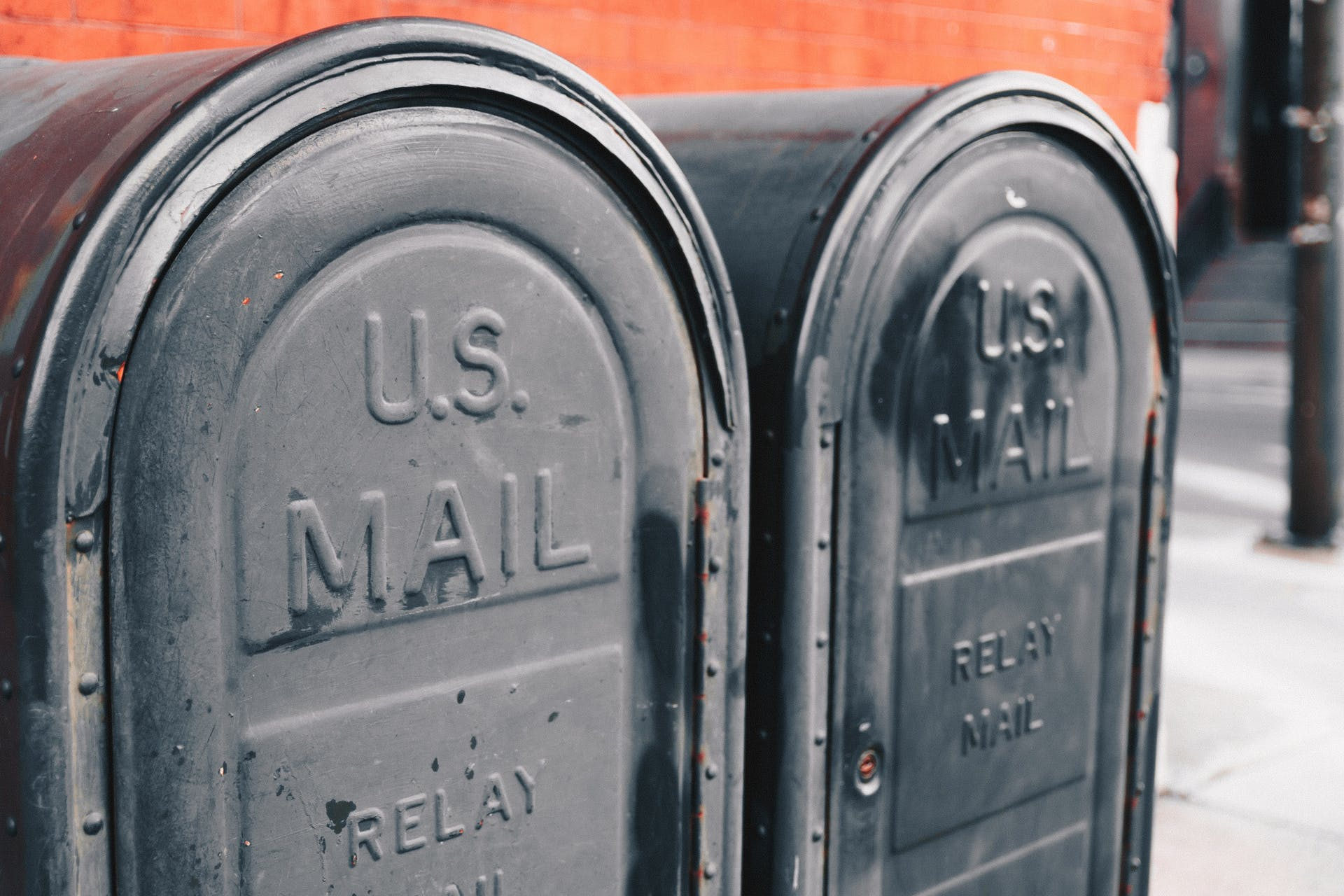 Two grey mail boxes on a city sidewalk. This image is being used as a thumbnail for a blog on direct marketing.