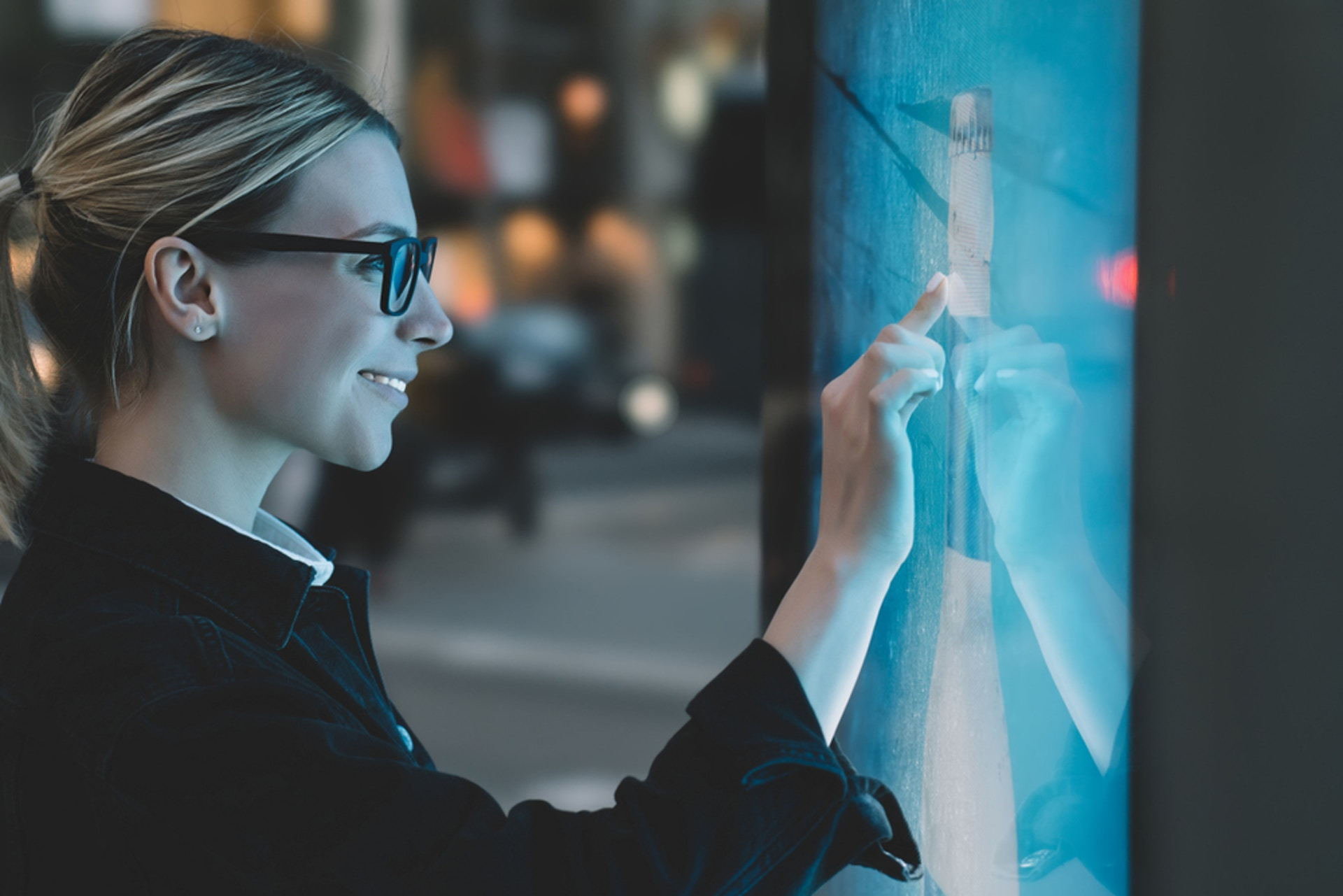 Smiling business woman standing in front of a large touch screen, manipulating data.