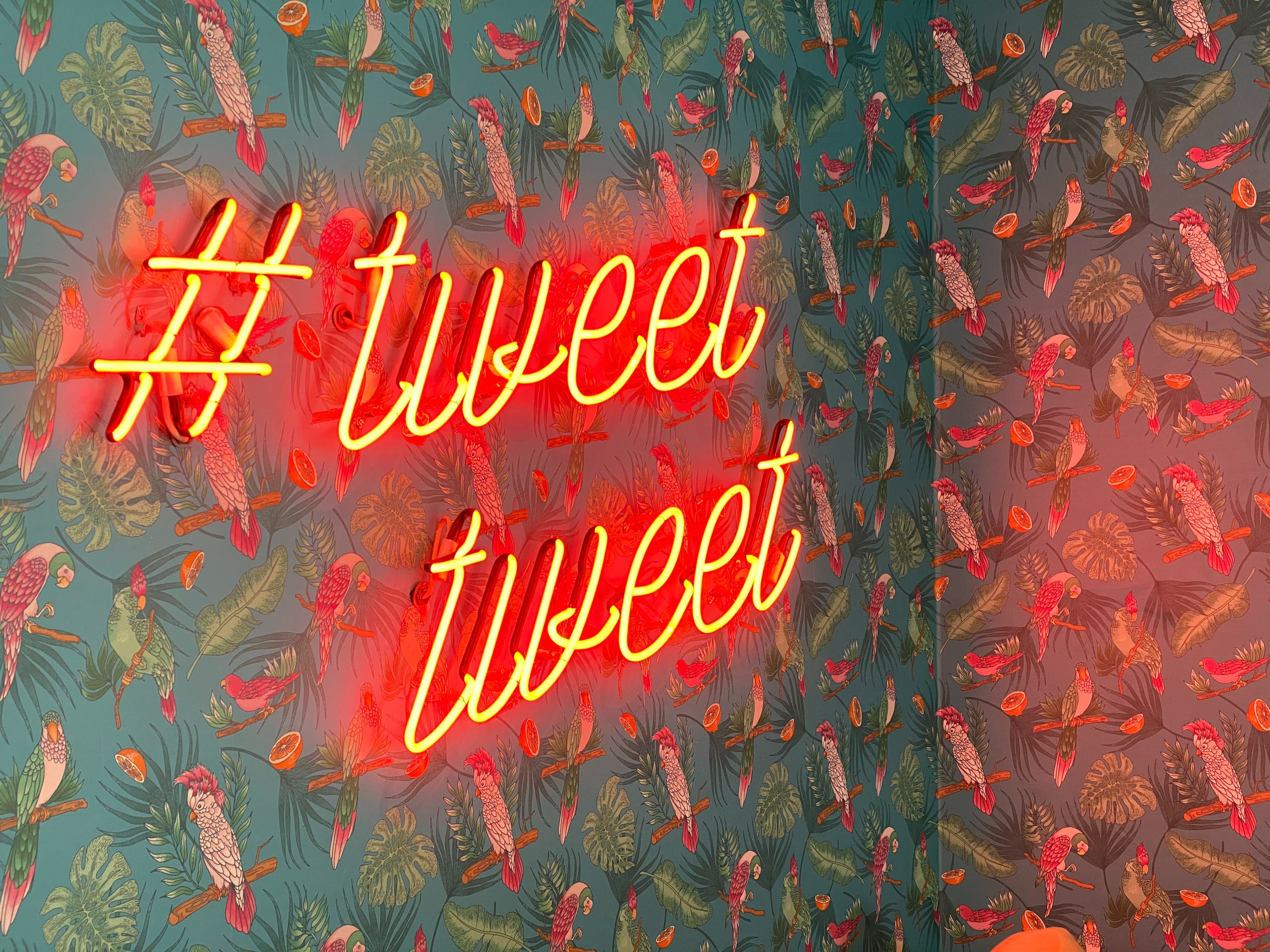 Neon sign with hashtag and two words saying Tweet