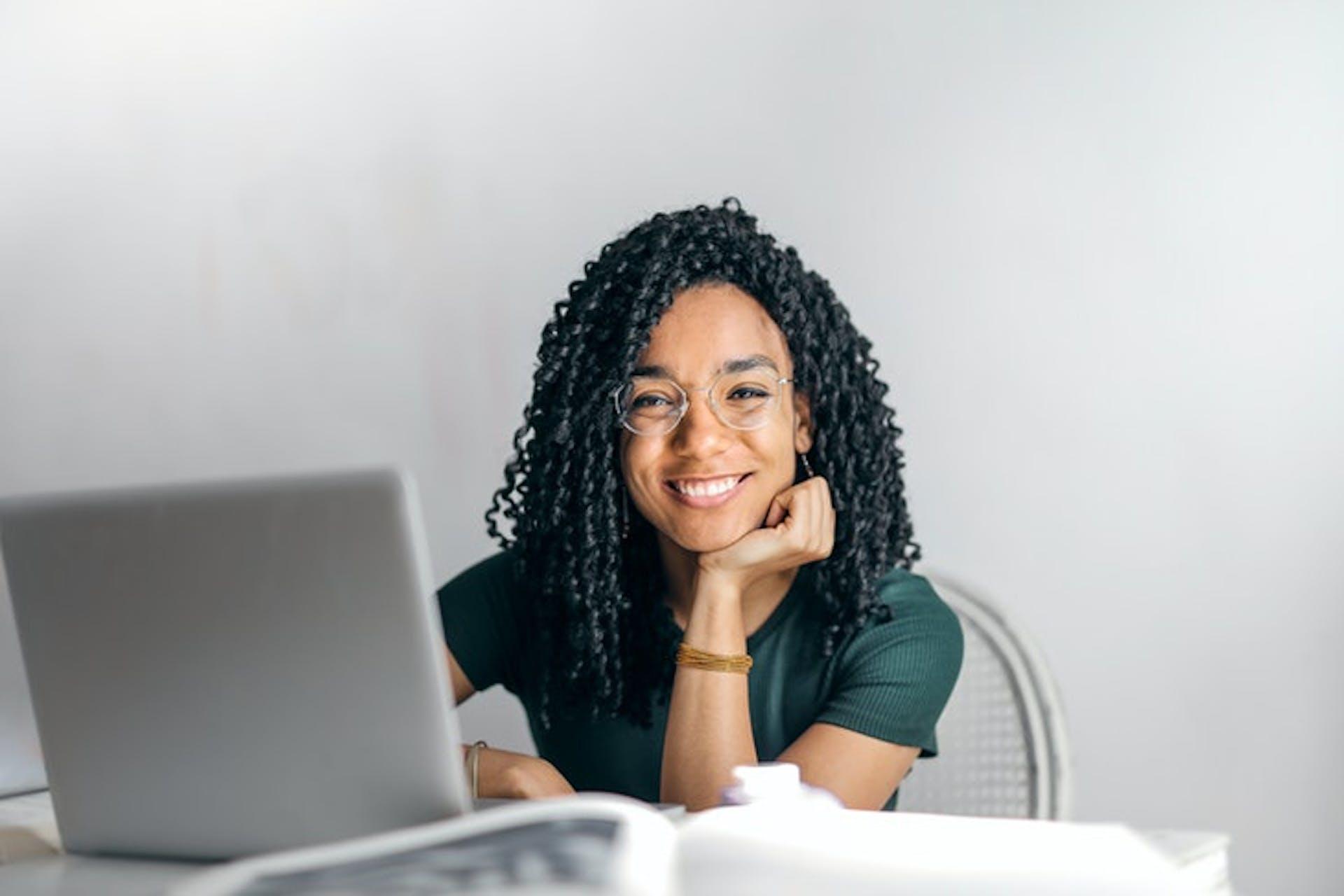 Eine lächelnde junge Frau sitzt vor einem Notebook.
