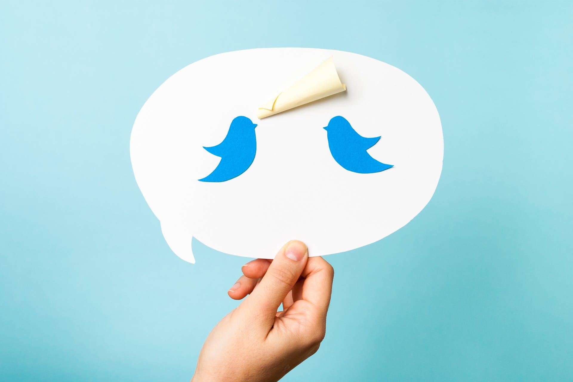 Käsi pitelemässä puhekuplaa, jonka sisällä kaksi lintua, jotka ovat myös Twitterin logoja.