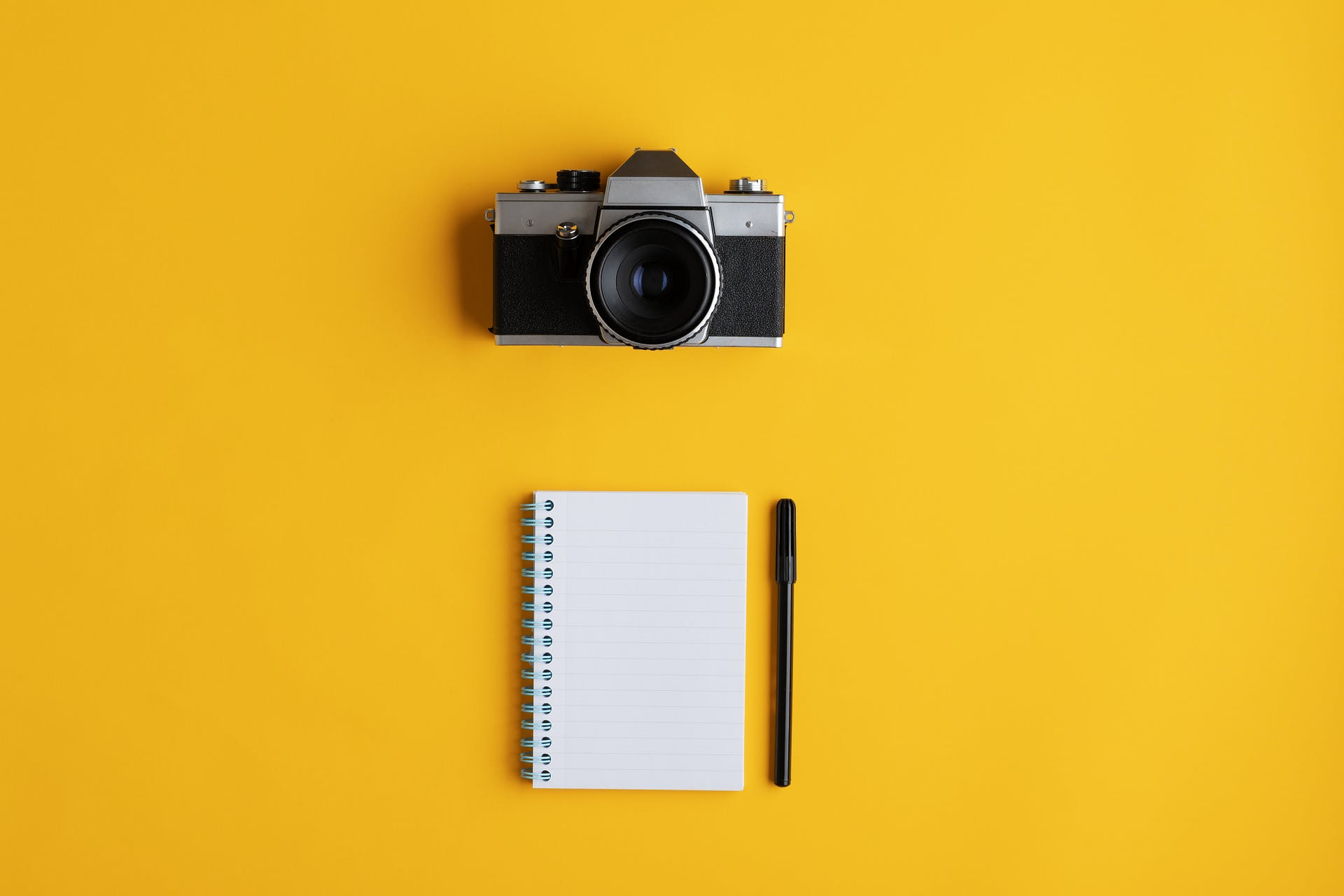 An image of a camera and a notepad on yellow background.