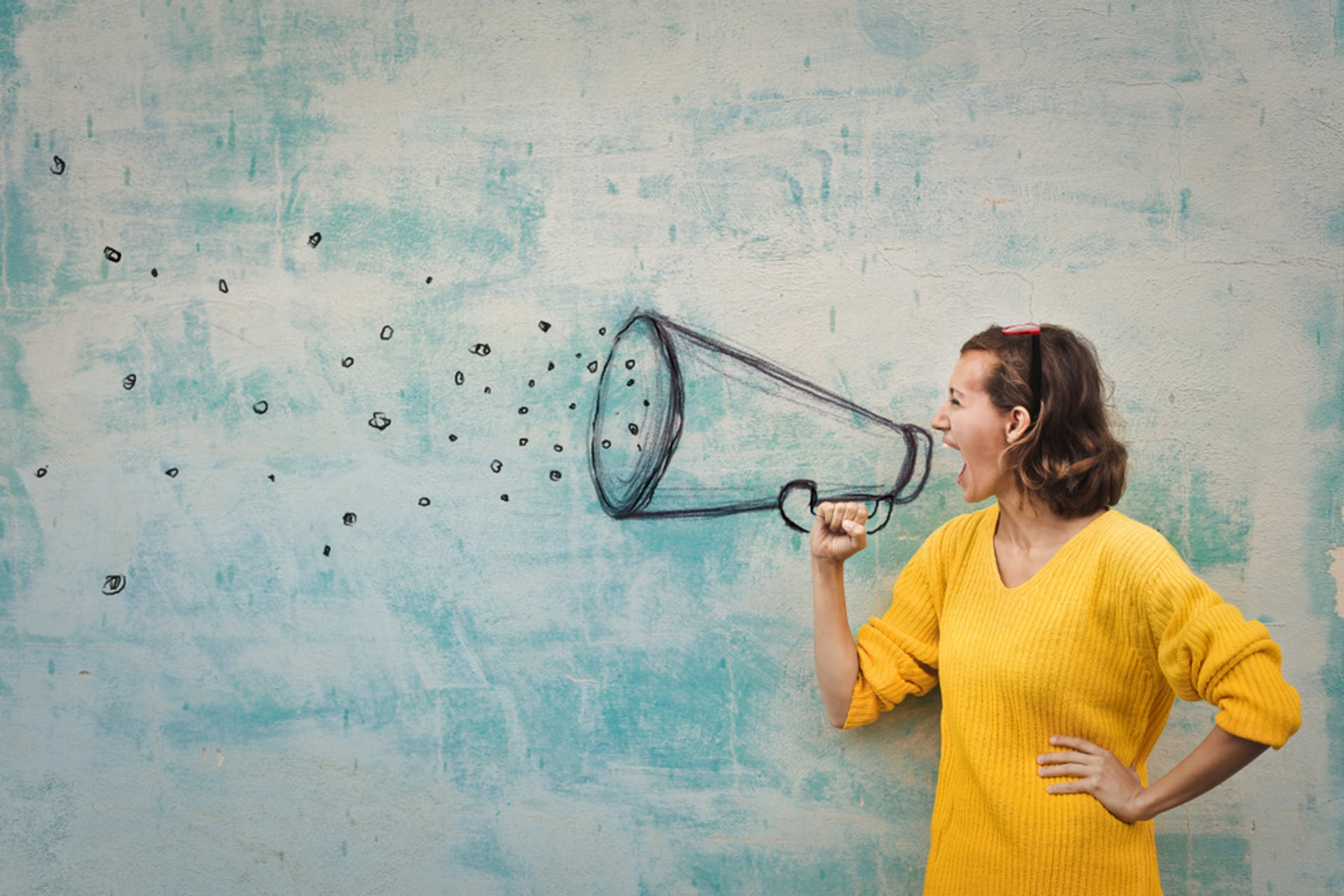 Frau ruft in ein gemaltes Megafon als Symbol für Markenbotschafter, Brand Advocates, Brand Ambassadors