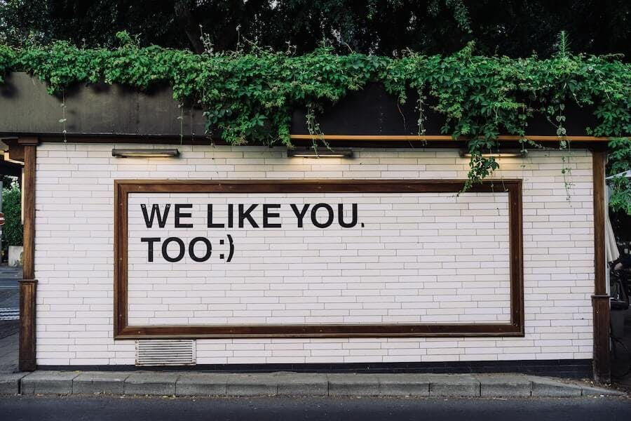 """A white brick wall with the text """"We like you, too :)"""" on it as an example for how to emotionalize people with marketing messages in guerrilla marketing."""