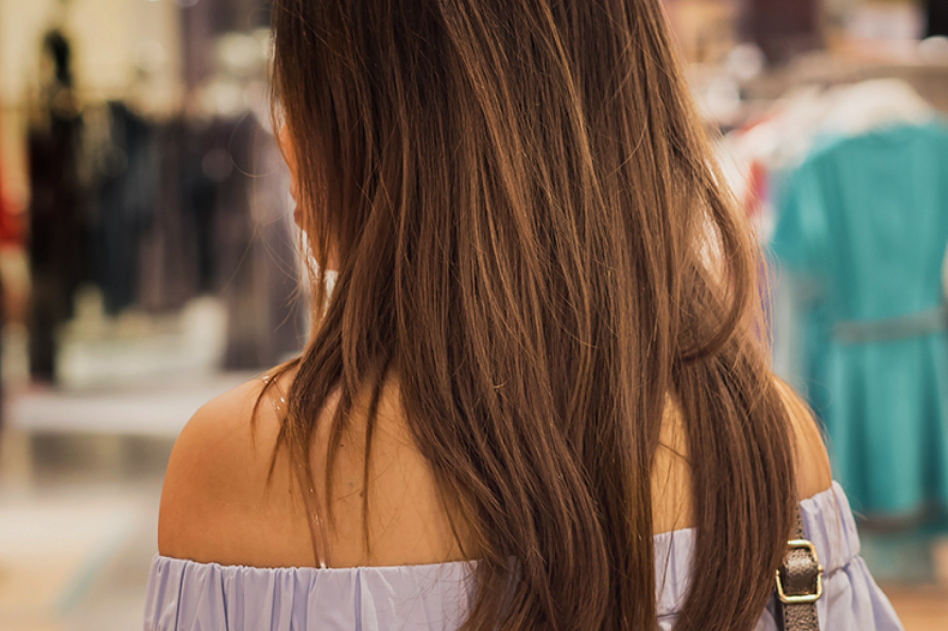 Back view of a brunette woman wearing an off-shoulder top
