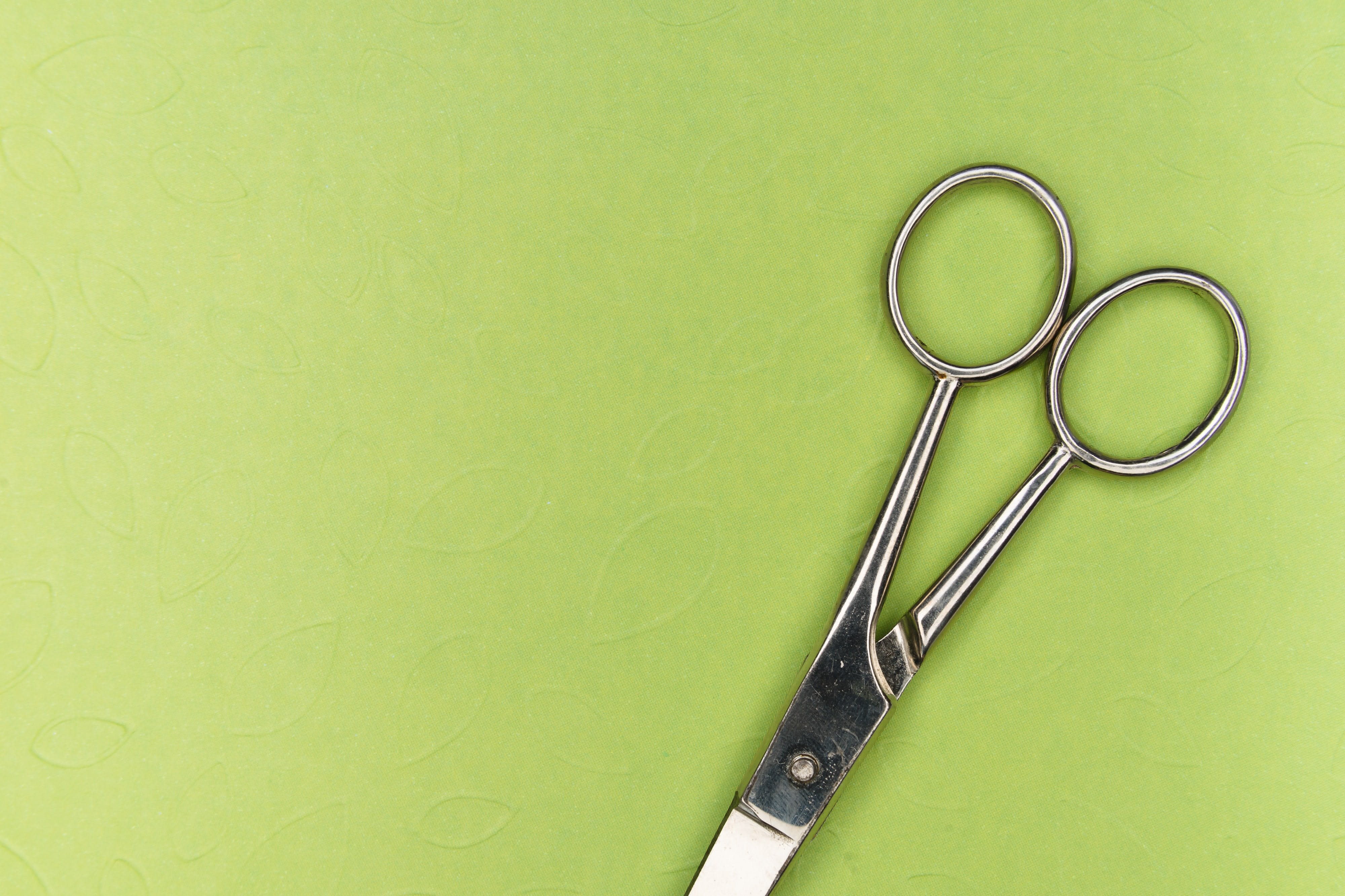Pair of scissors on green background
