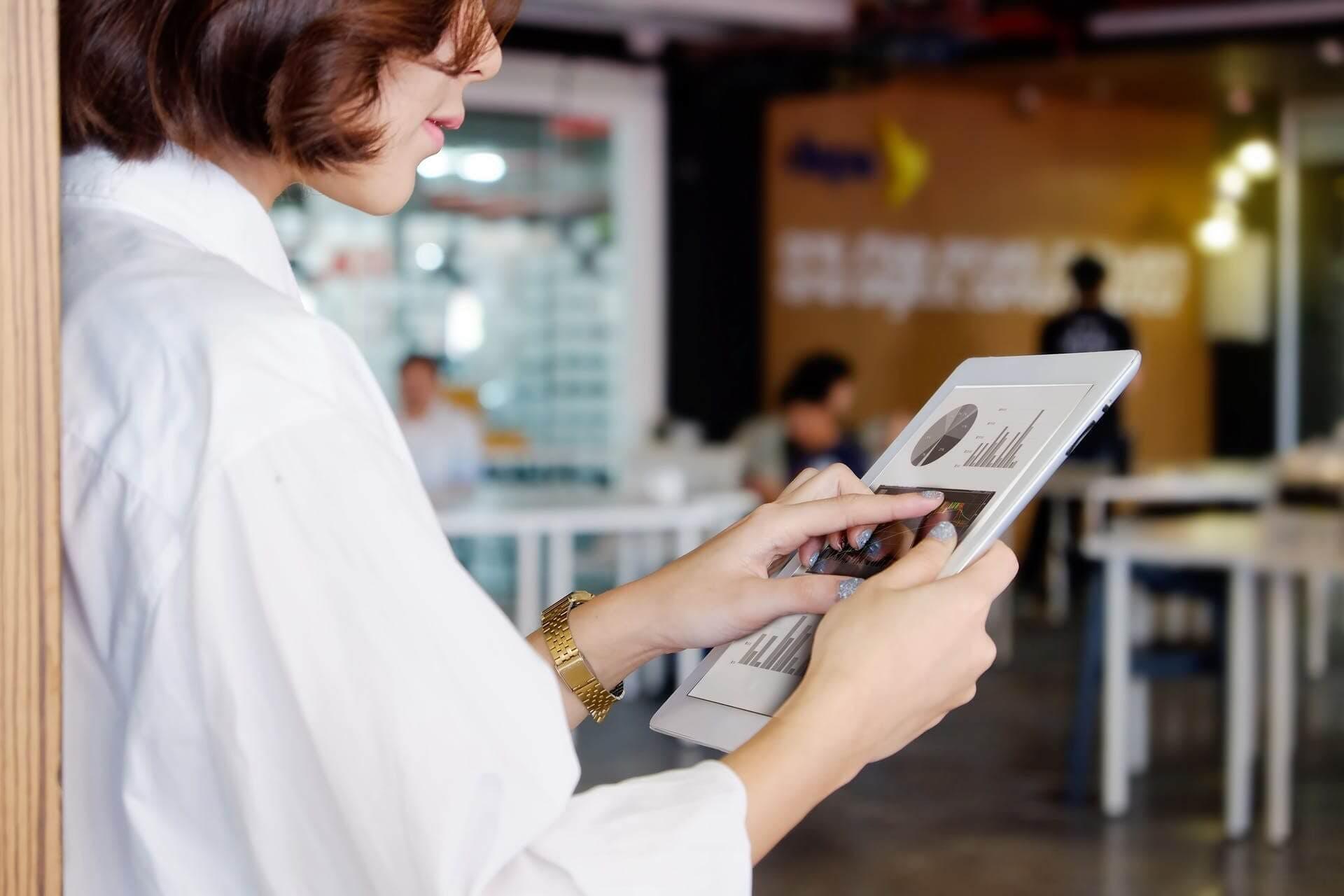 Femme avec une chemise blanche qui tient un ipad avec des graphiques