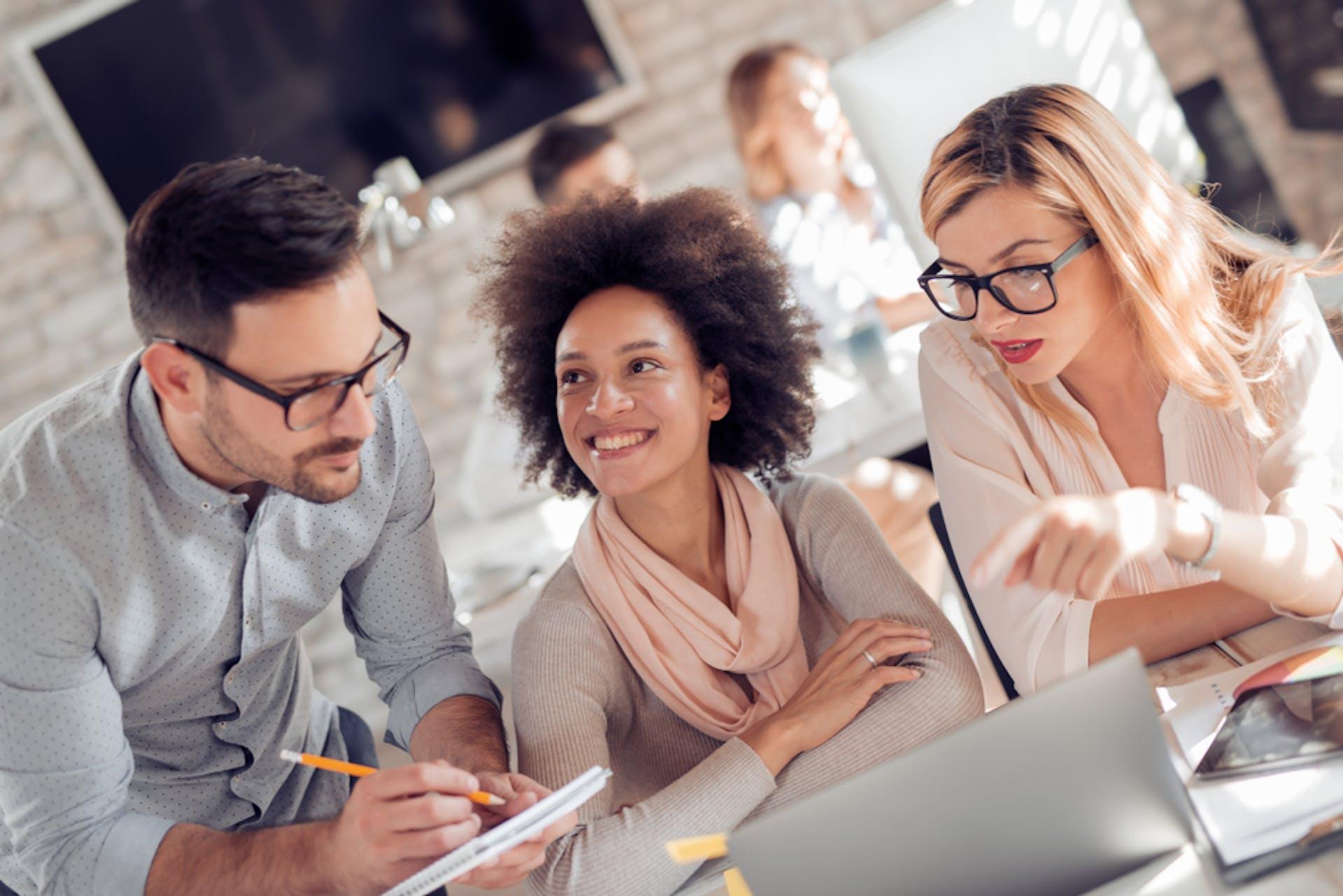 Arbeitskollegen besprechen etwas als Headerbild zu unserem Beitrag zu 4 Ps und 7 Ps im Marketing-Mix