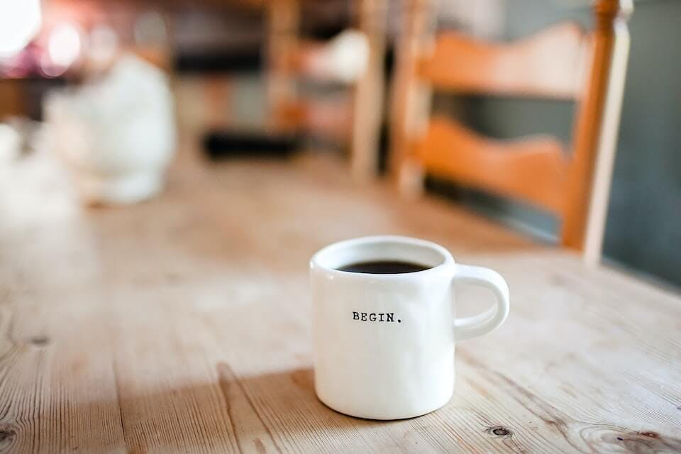 """photo of a coffee mug on a table with the writing """"begin"""""""