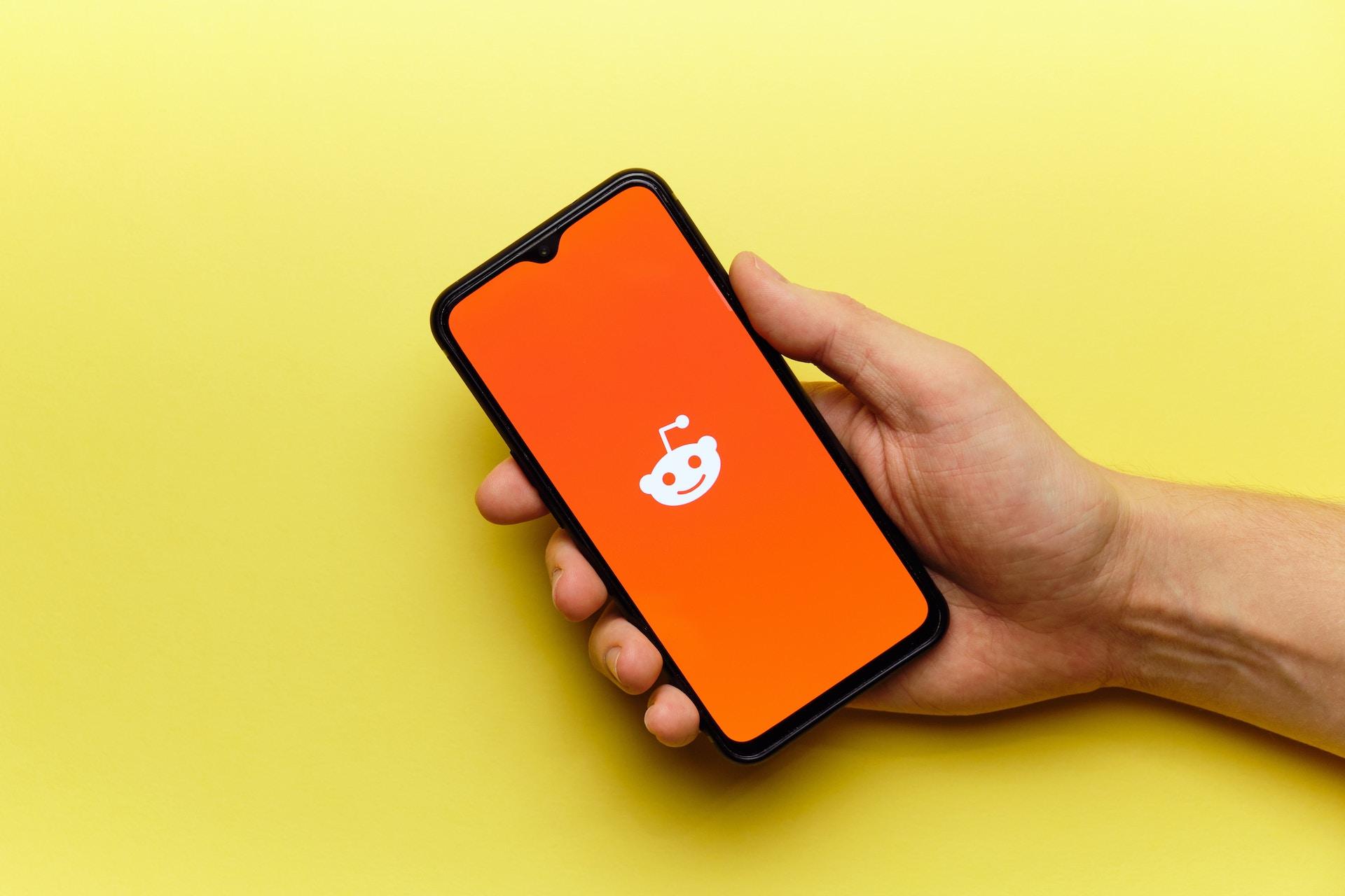 Auf einem gelben Hintergrund hält eine Hand ein Handy auf dem Mann das weiße Reddit-Symbol auf orangenen Hintergrund sieht