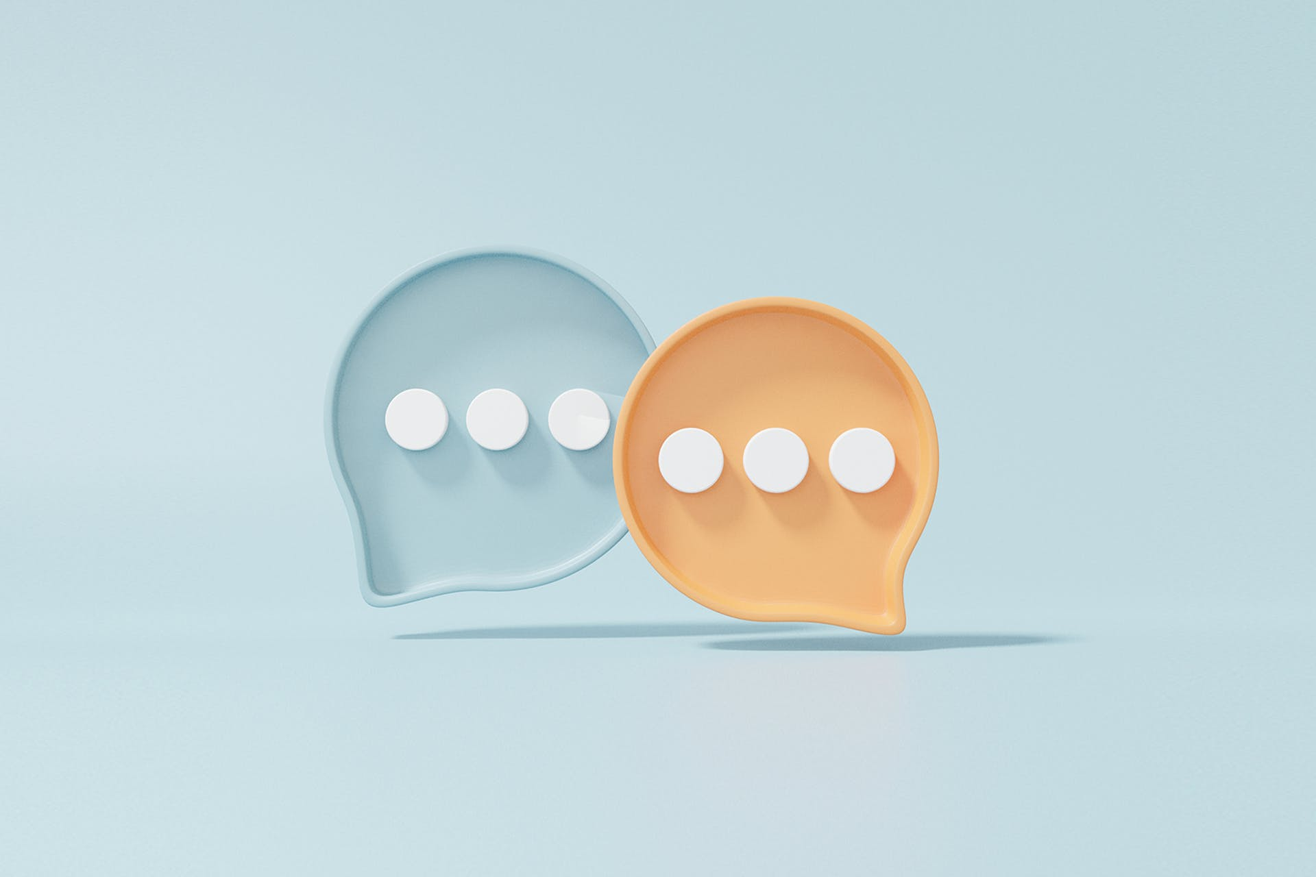 Two chat bubbles (one orange and one blue) are floating in the center of the image. Maintaining open lines of communication is essential for businesses to operate smoothly. This blog explains the importance of internal communications for businesses and the various tactics companies can use to ensure information is following throughout departments.