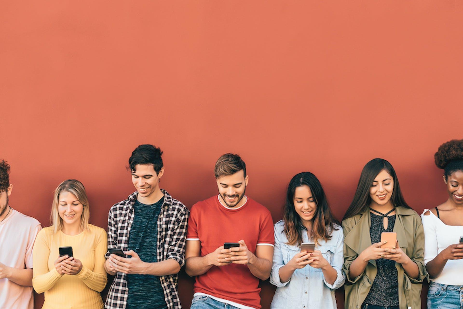 Junge Leute schauen fröhlich auf ihr Handy während sie an einer orangen Wand lehnen