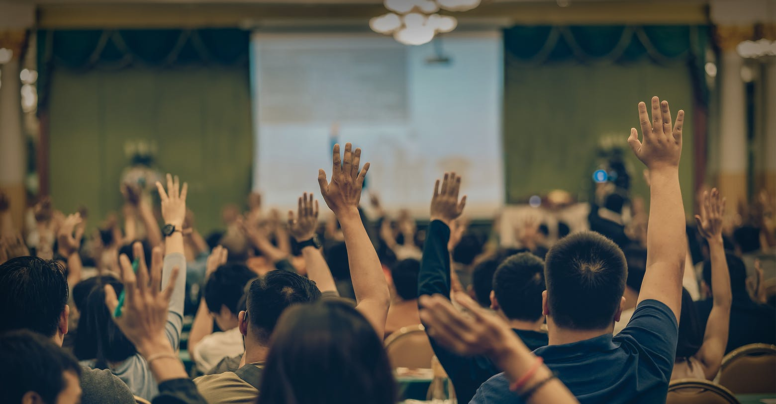 A room of people with hands in the air to ask questions