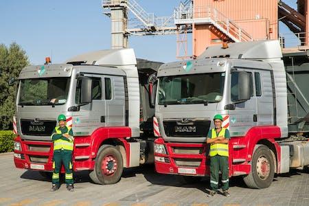 Employés de carrières et transport Ménara devant des camions de la société.