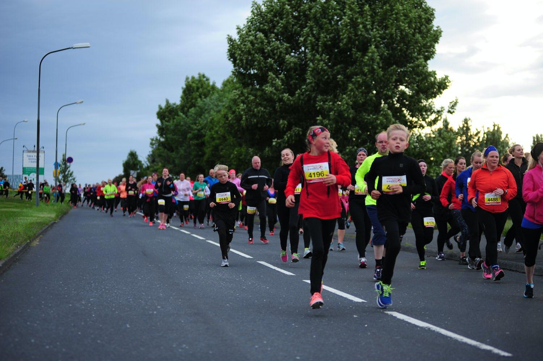 Participants in the Suzuki Midnight Sun Run running down road Engjavegur