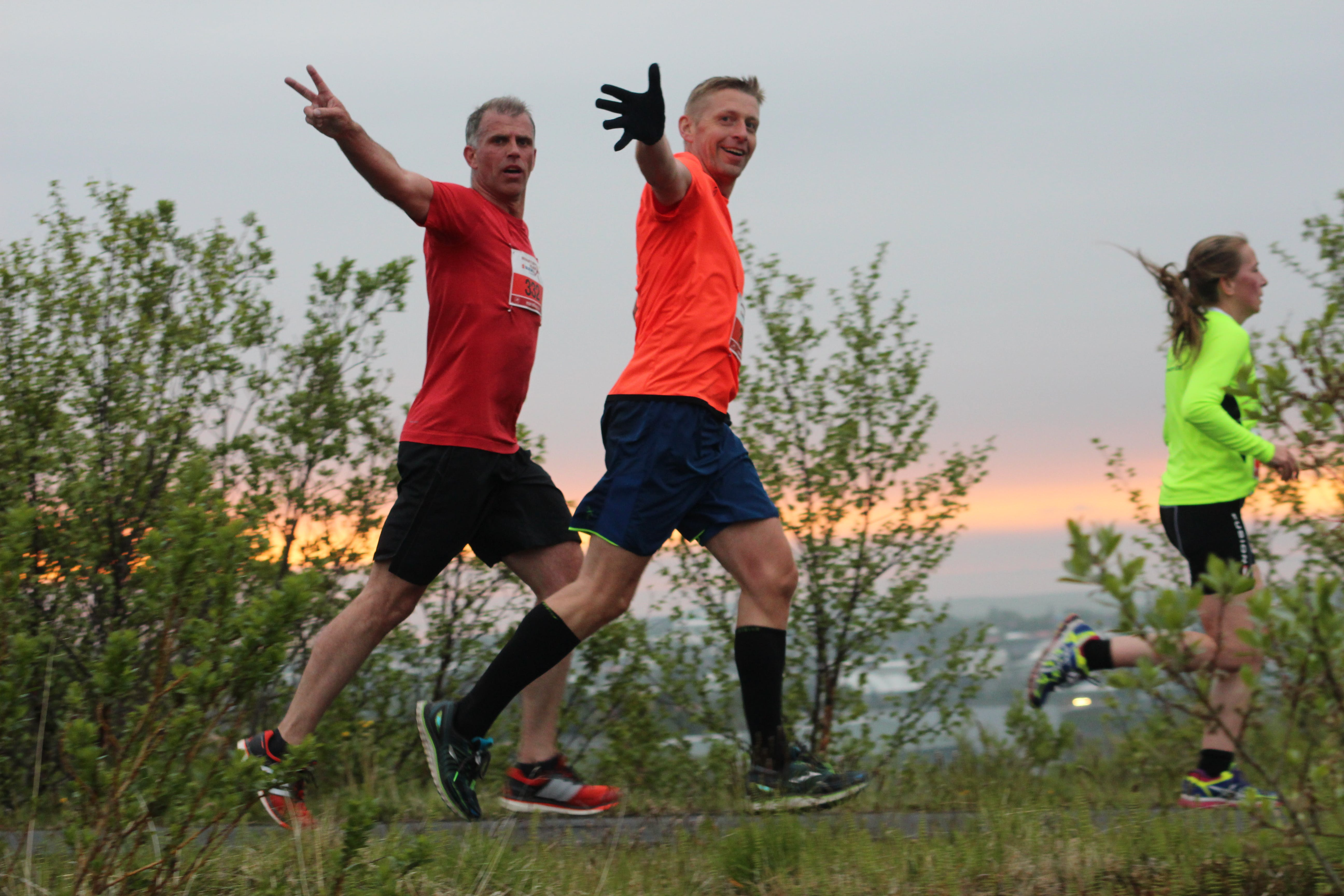 Happy participants running in the midnight sun