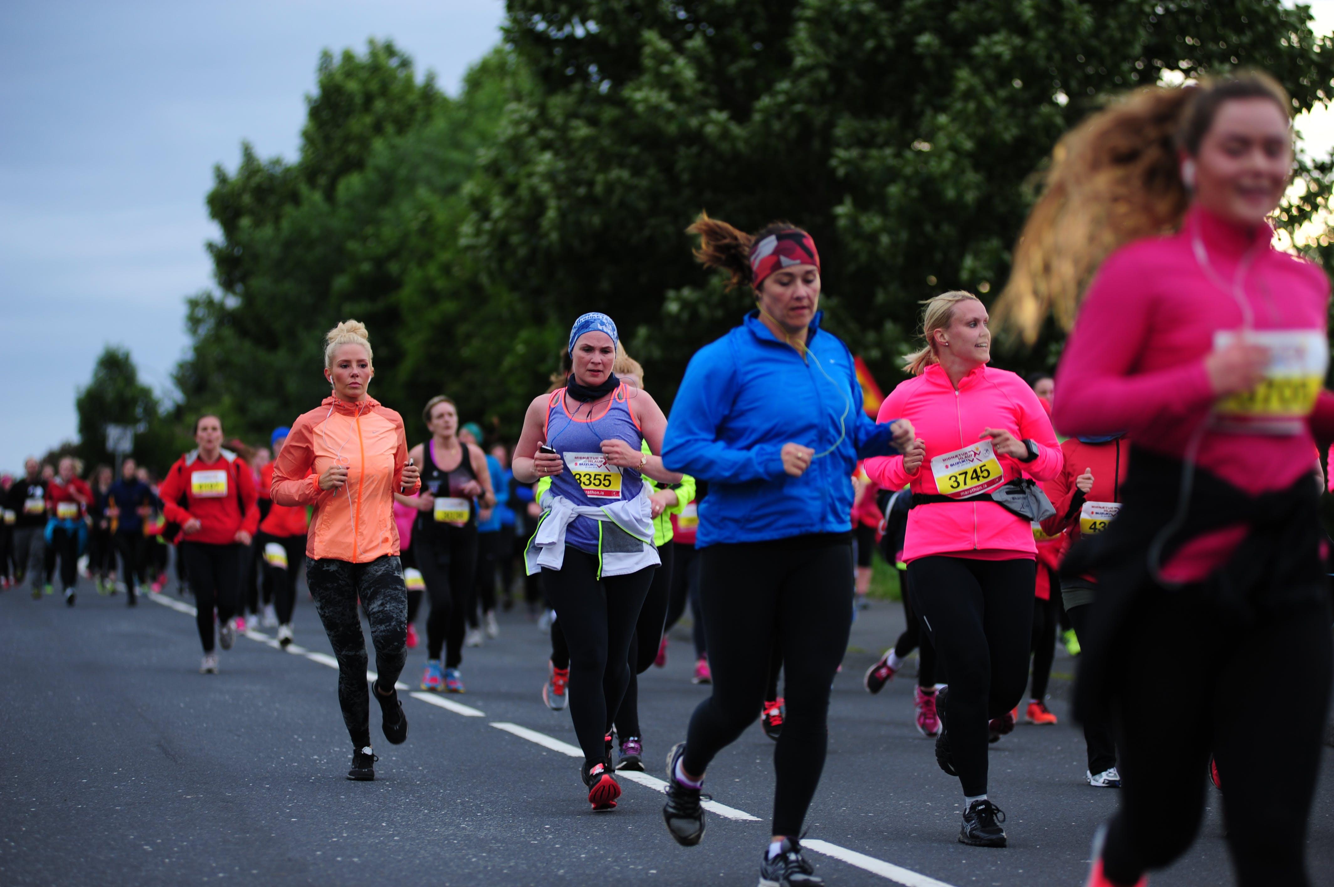 Female participants running down road Engjavegur