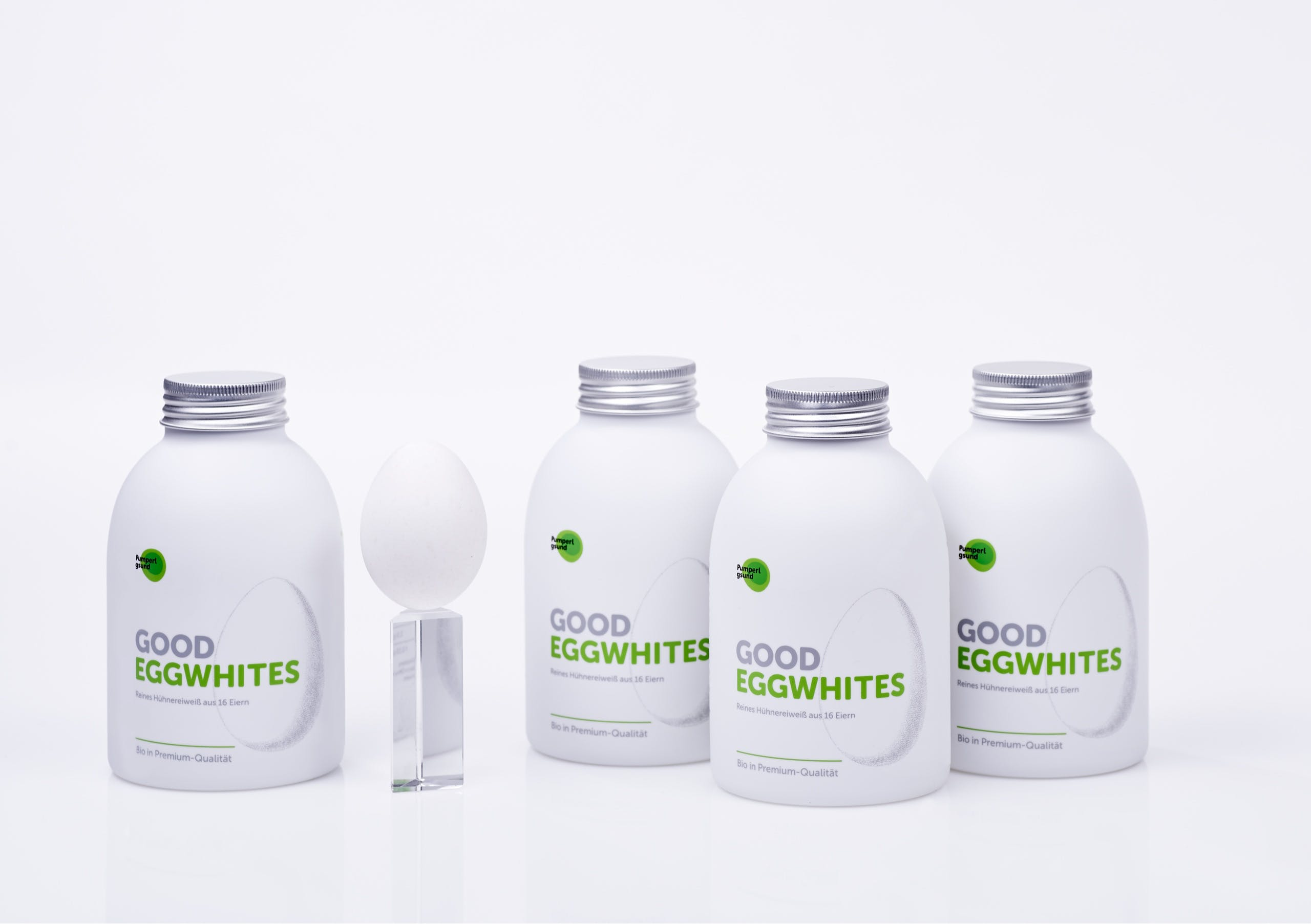 Four white Pumperlgsund bottles with 'good eggwhites' branding and one white egg standing on glass bar, showing packaging