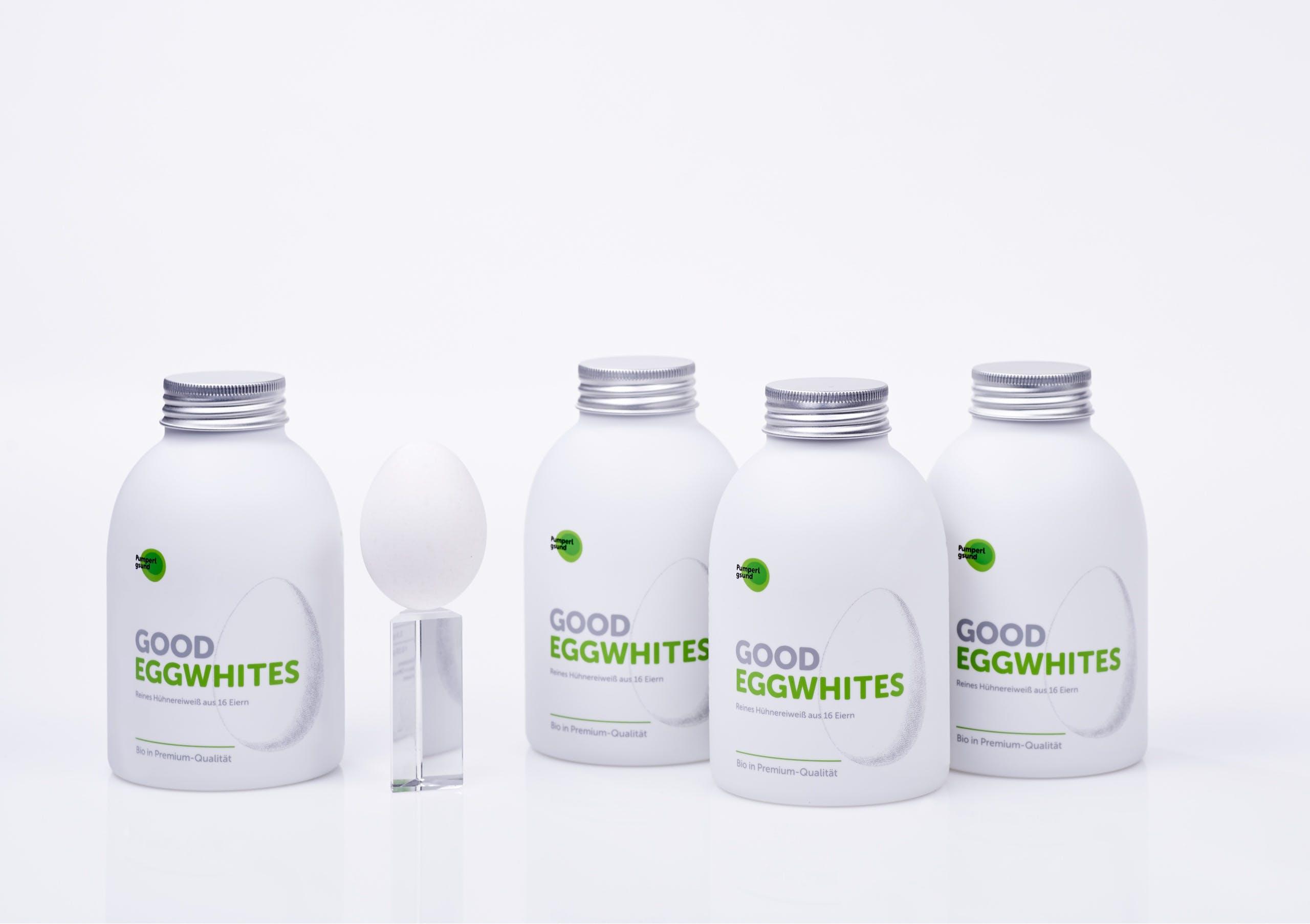 Four white Pumperlgsund bottles with 'good eggwhites' branding and one white egg standing on glass bar, showing packaging