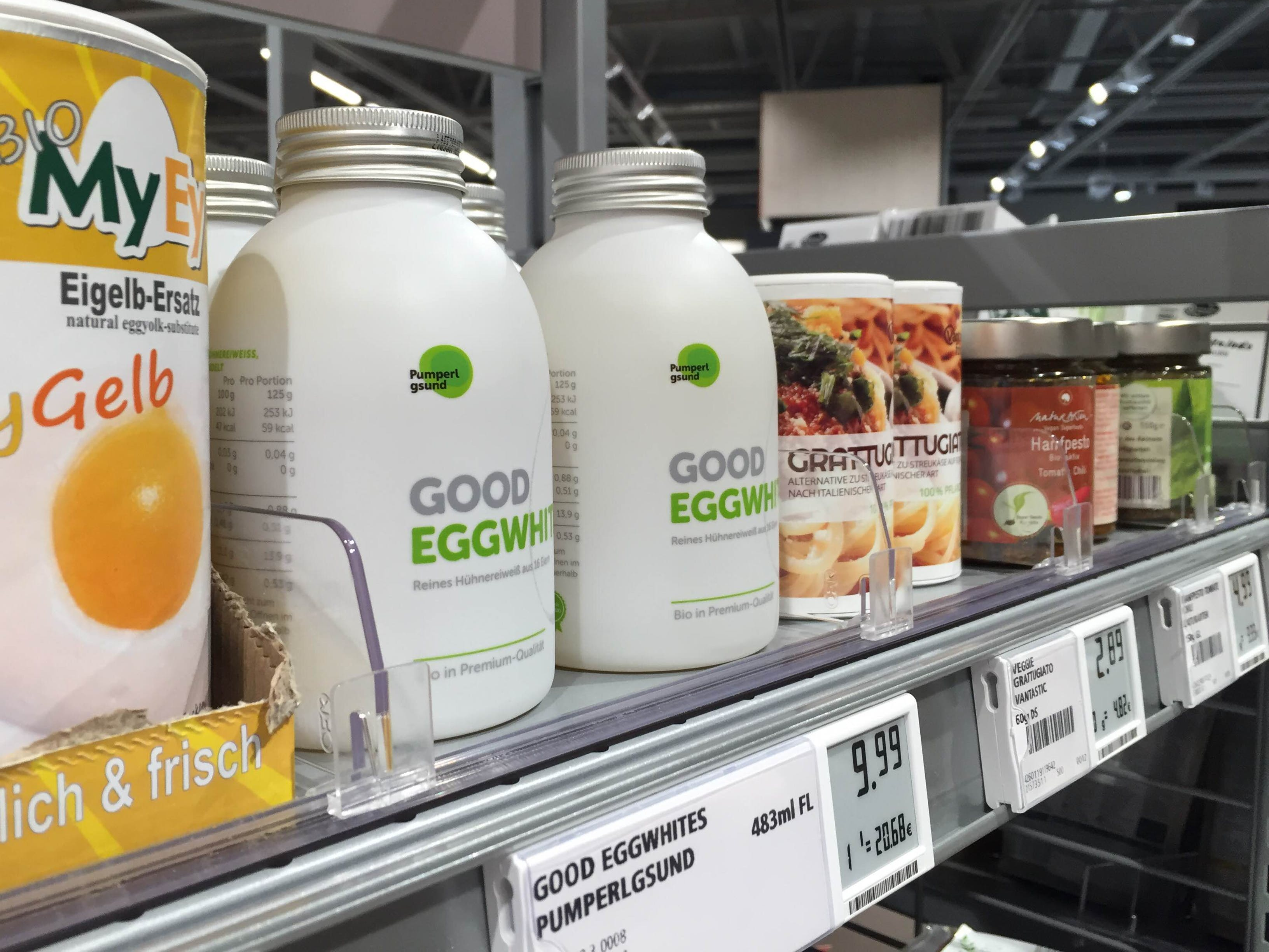 White branded bottles with good eggwhites from Pumperlgsund shown on supermarket shelf next to spicery