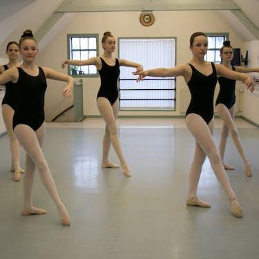 Tieners in een balletpositie tijdens een van de klassiek balletlessen.