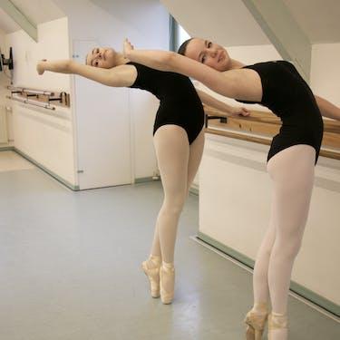 Danseressen op spitzen in een cambré aan de barre in een van onze klassiek balletlessen.