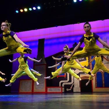 Dansers van Balletstudio Mirjam Ouwerkerk die een grote sprong maken tijdens een voorstelling in het theater.